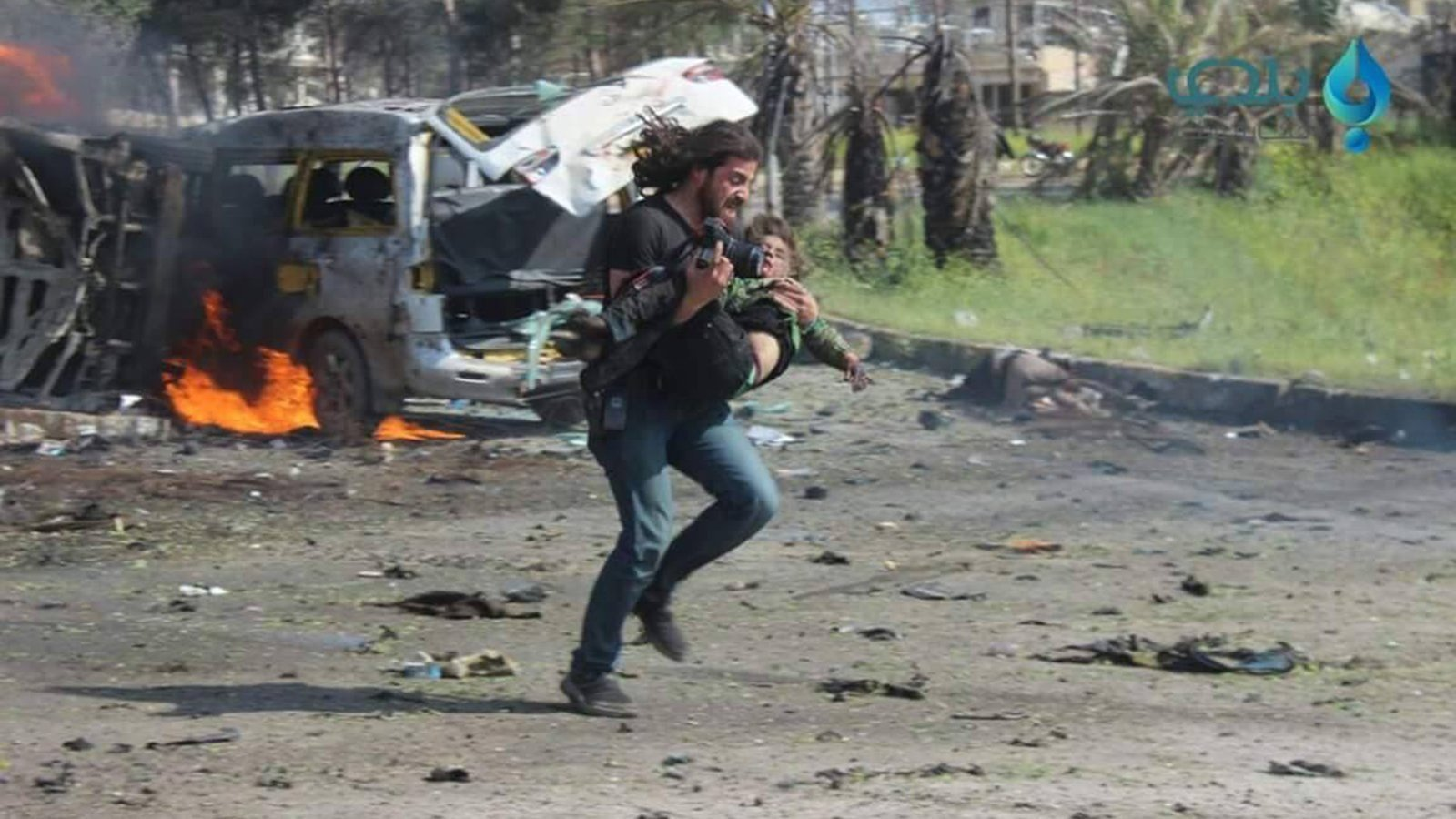 Syria photographer puts down camera, picks up injured boy