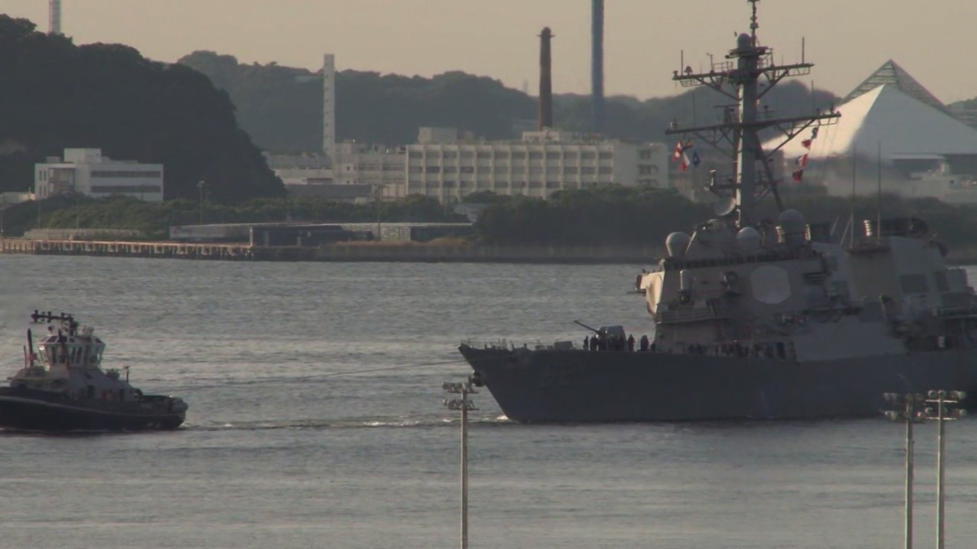 The damaged USS Fitzgerald is being towed by a tugboat in the waters near the U.S. Naval base in Yokosuka.