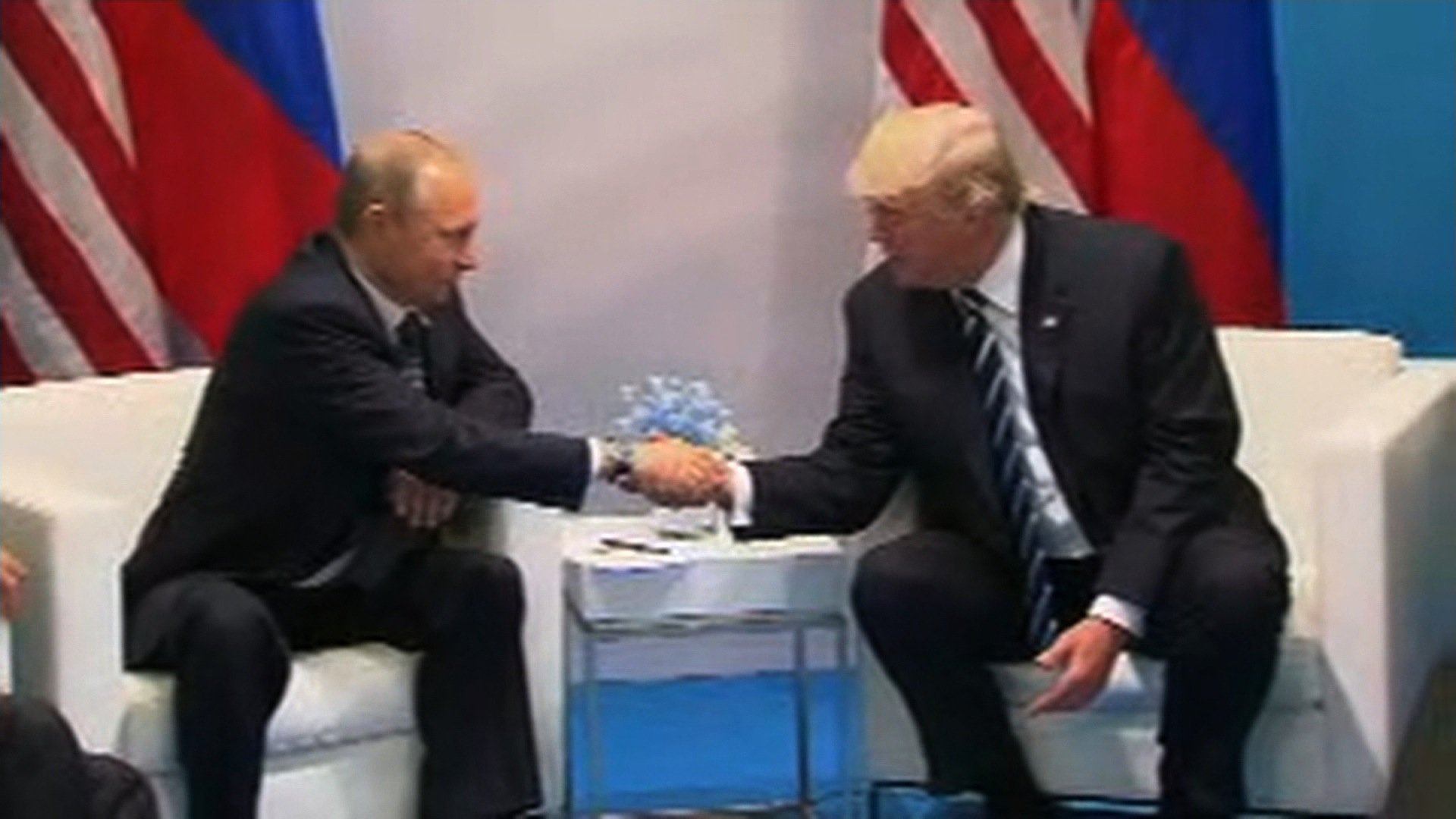 President Donald Trump and Russian President Vladimir Putin shake hands