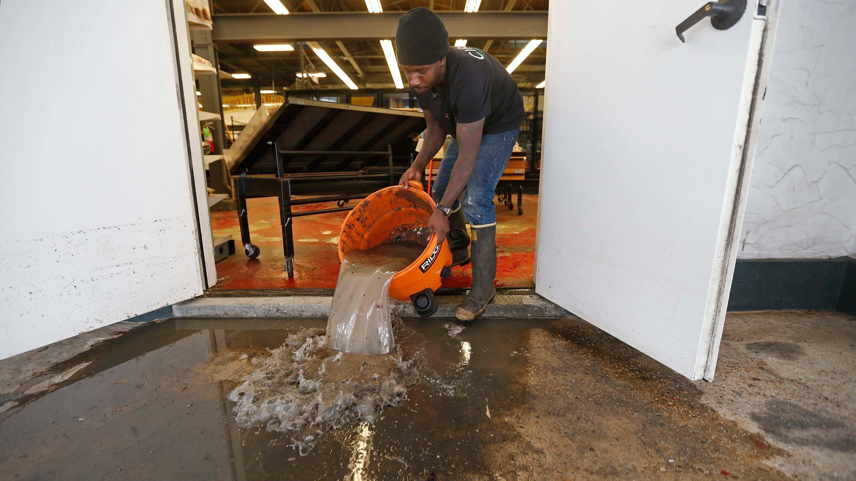 Dwayne Boudreaux Jr., the owner of Circle Food Store, dumps out dirty water Monday that was vacuumed up from the store after weekend flooding in New Orleans.  This image is for use with this specific article only.