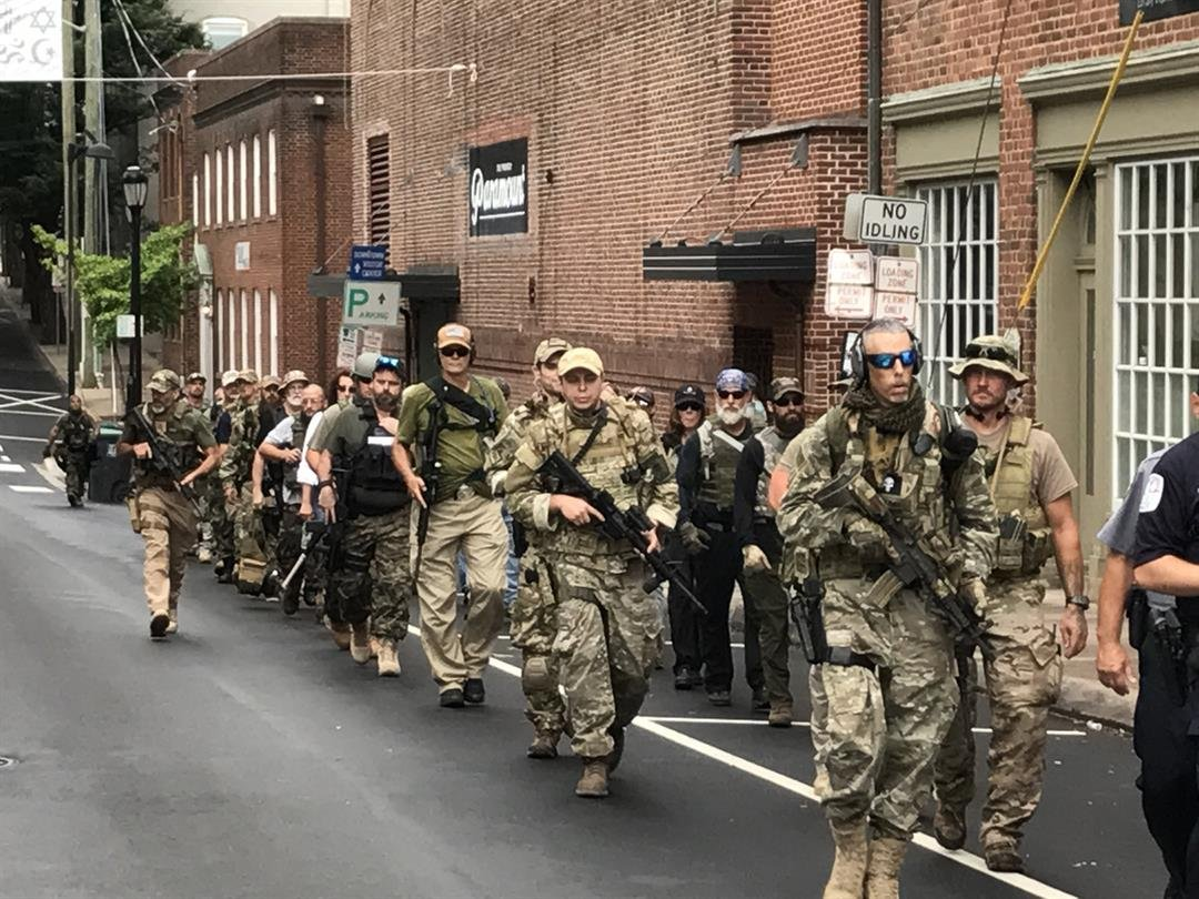 Several members of an alt right group have gathered in Charlottesville, Va to express their first amendment rights. In the photos, you can see a group people being escorted by authorities carrying long guns as they walk through the streets of Virginia.