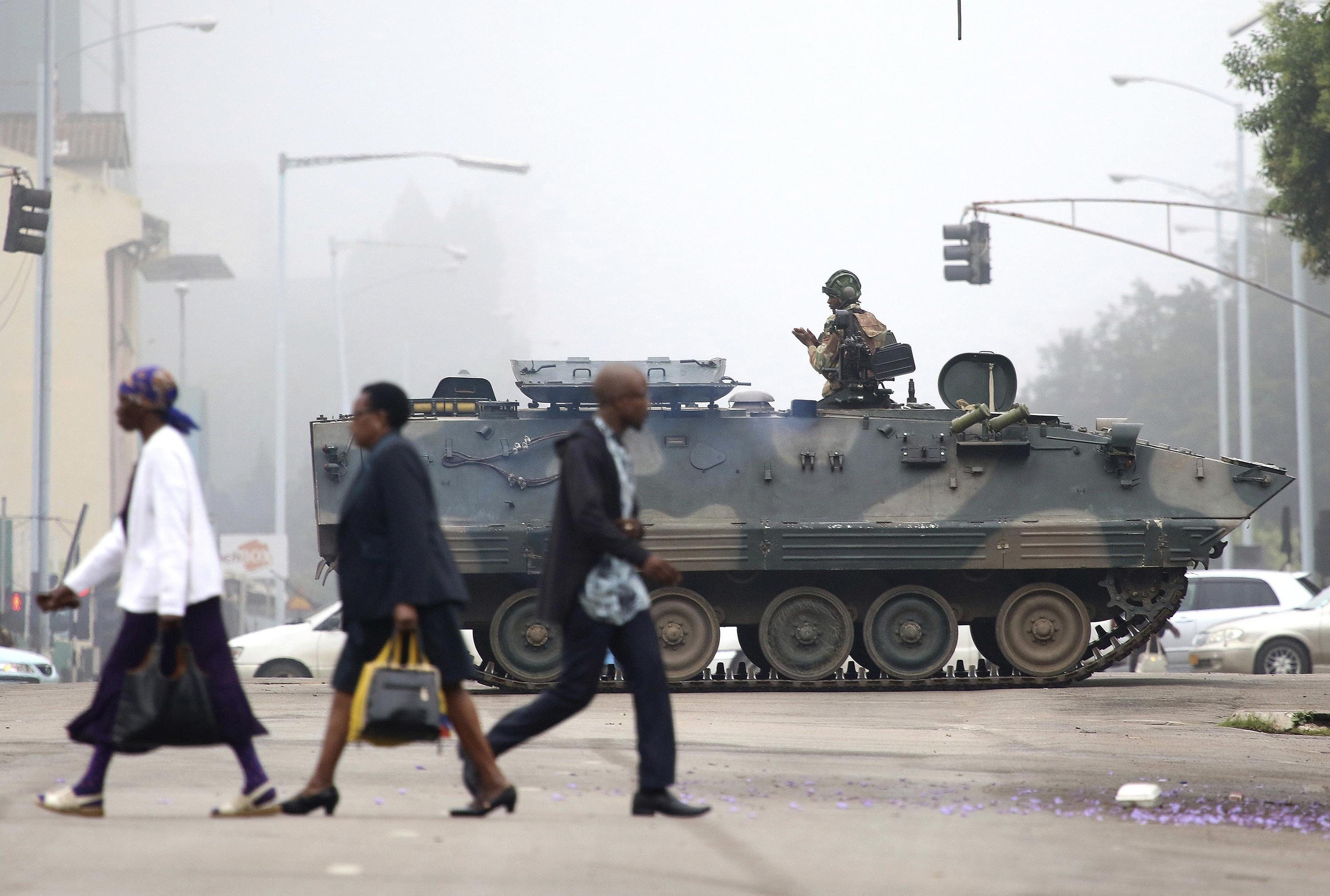 **This image is for use with this specific article only**  A tank patrols a street in Harare on Wednesday, November 15, after an apparent coup in Zimbabwe. In a dramatic televised statement, an army spokesman denied that a military takeover was...