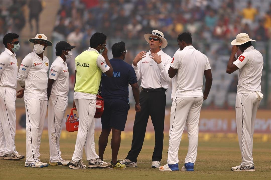 **This image is for use with this specific article only.**  Officiating umpire Nigel Llong, third from right, addresses Sri Lanka's players wearing masks, during a brief break on Sunday's match.