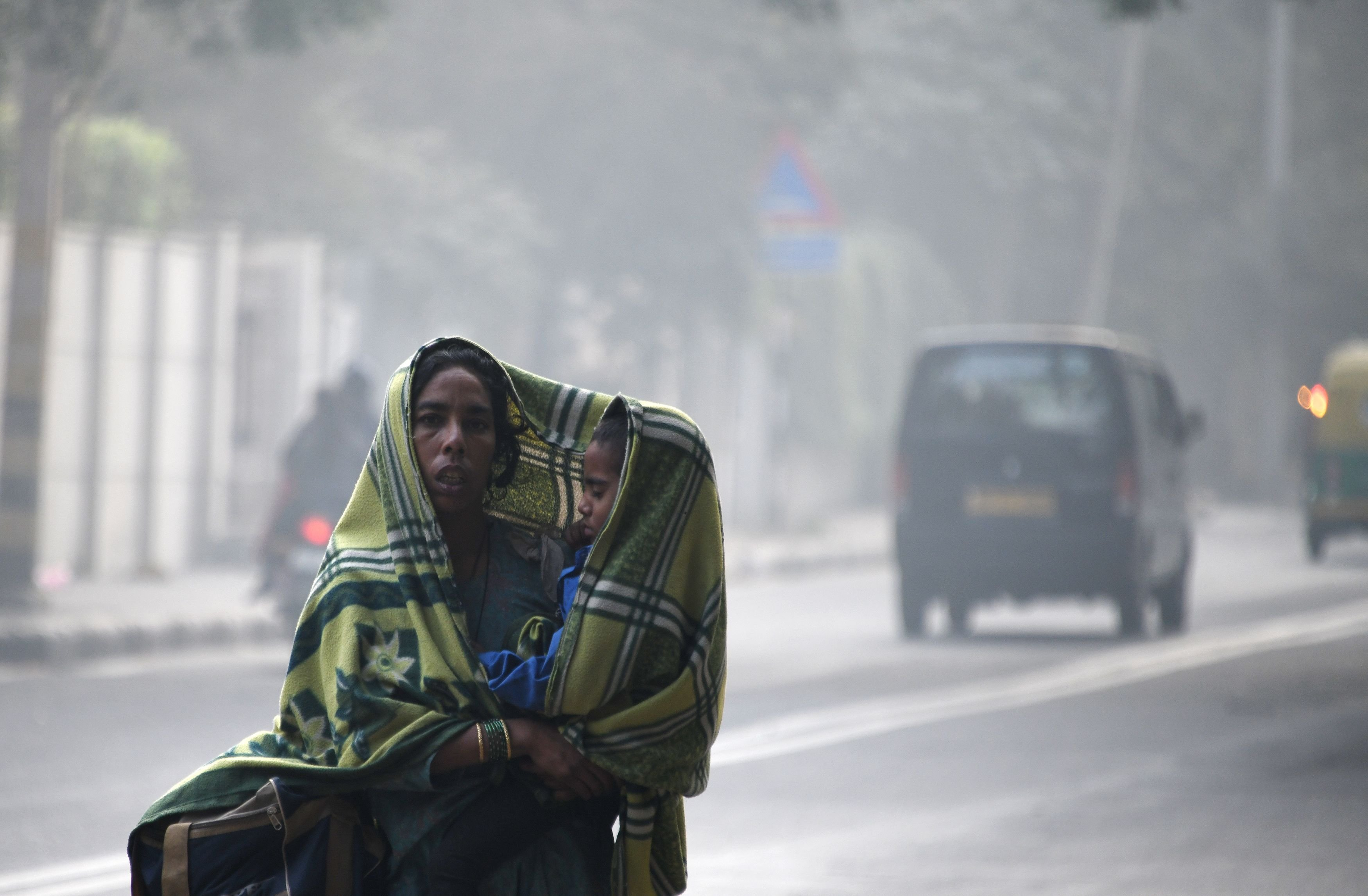 **This image is for use with this specific article only.**  An Indian woman and her child walk amid heavy smog on a street in New Delhi on December 4, 2017.
