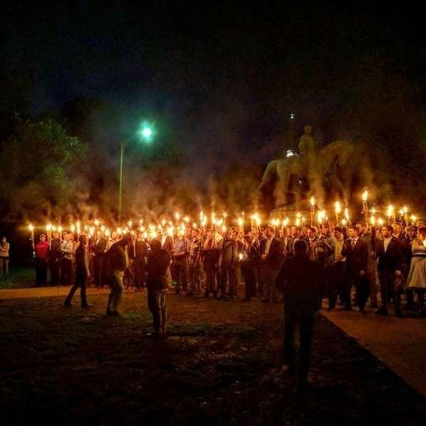 Torch-carrying demonstrators gather in Charlottesville on Saturday to protest the statue's removal.