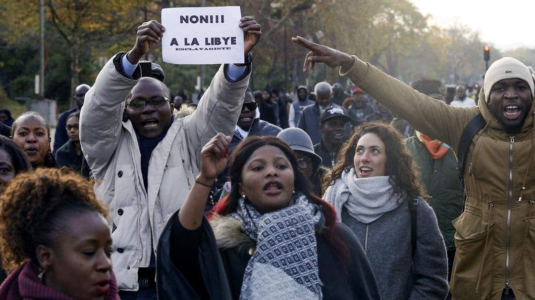 "**This image is for use with this specific article only.**  Credit: Geoffroy Van Der Hasselt/AFP/Getty Images  A man holds a placard reading ""No to slavery in Libya"" during a march against ""slavery in Libya"" on November 18 in Paris."