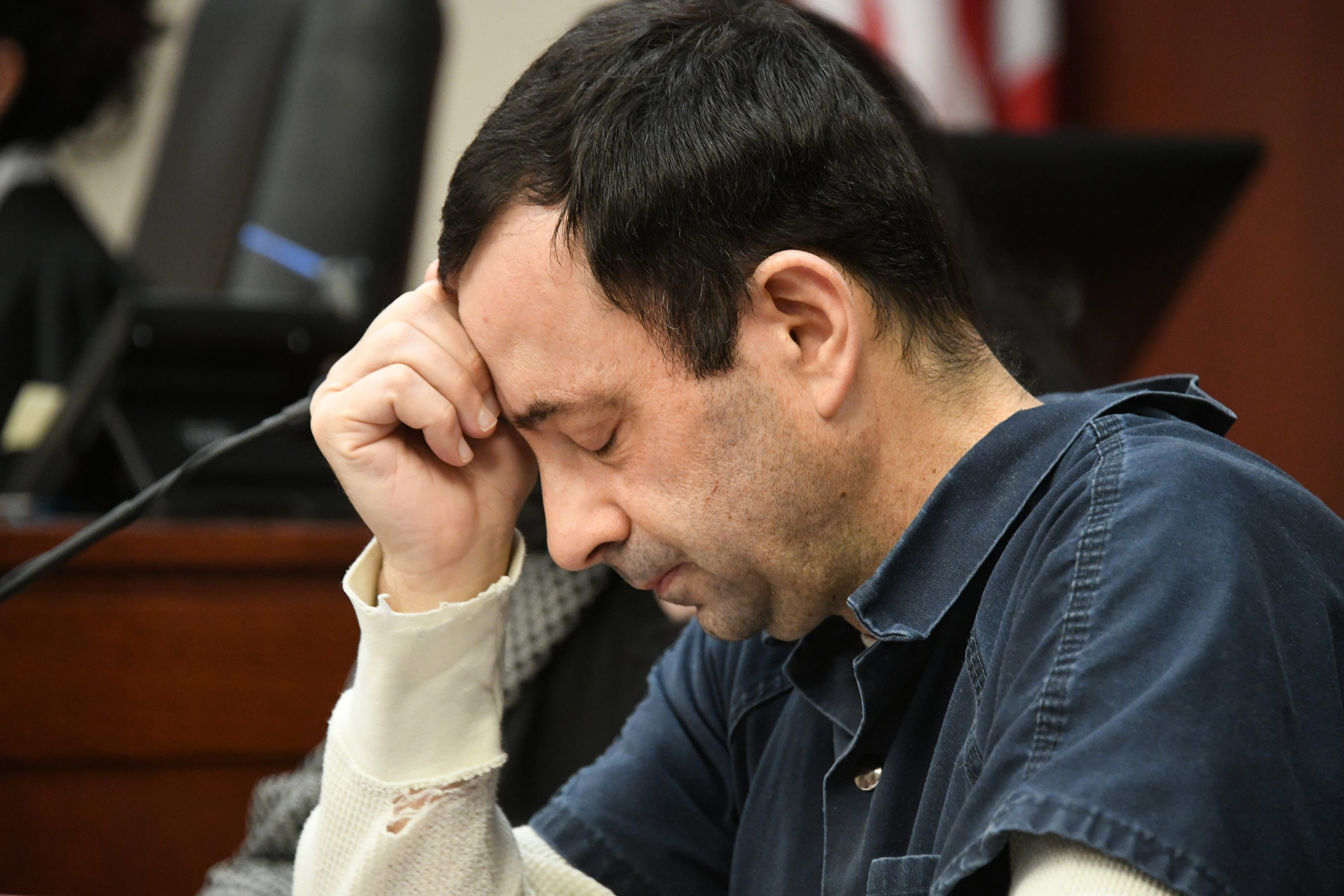 **This image is for use with this specific article only**  As he listened to the 169 impact statements, Larry Nassar sat on the witness stand, sometimes hiding his head in his hands or wiping away tears with a tissue.
