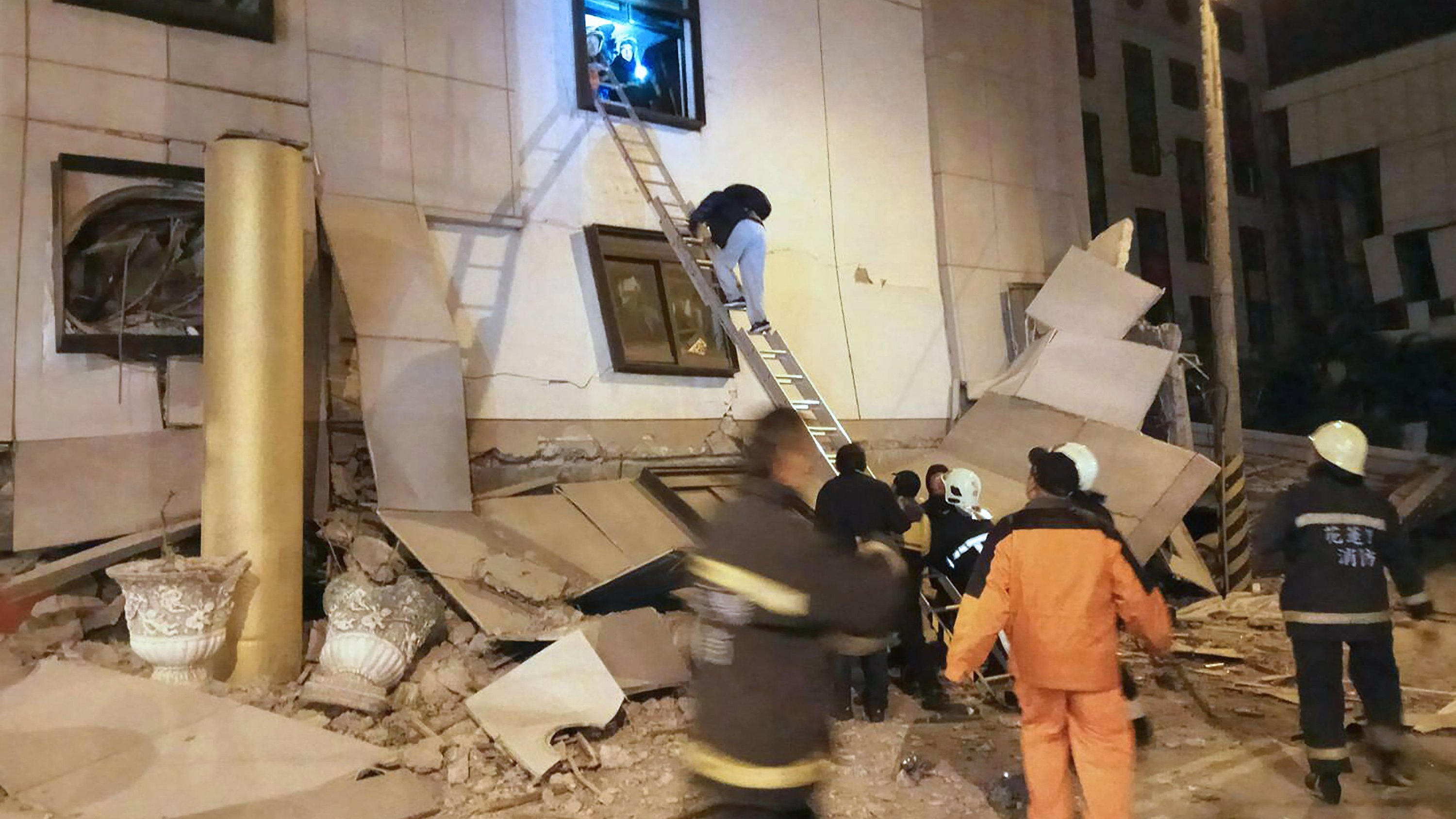 Rescue workers search through rubble outside the Marshal Hotel in Hualien, eastern Taiwan early February 7, 2018, after a strong earthquake struck the islan