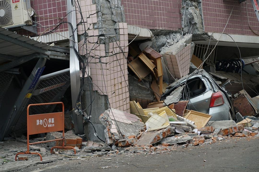 A car sits crushed under a building after a 6.4 magnitude quake hit the eastern Taiwanese city of Hualien, on February 7.