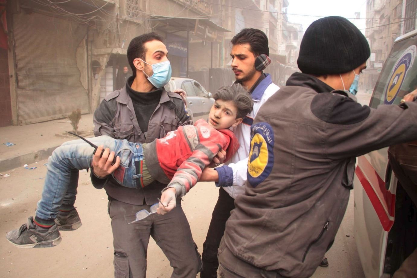 The White Helmets carry an injured child after strikes this week in Douma in Syria's Eastern Ghouta area.