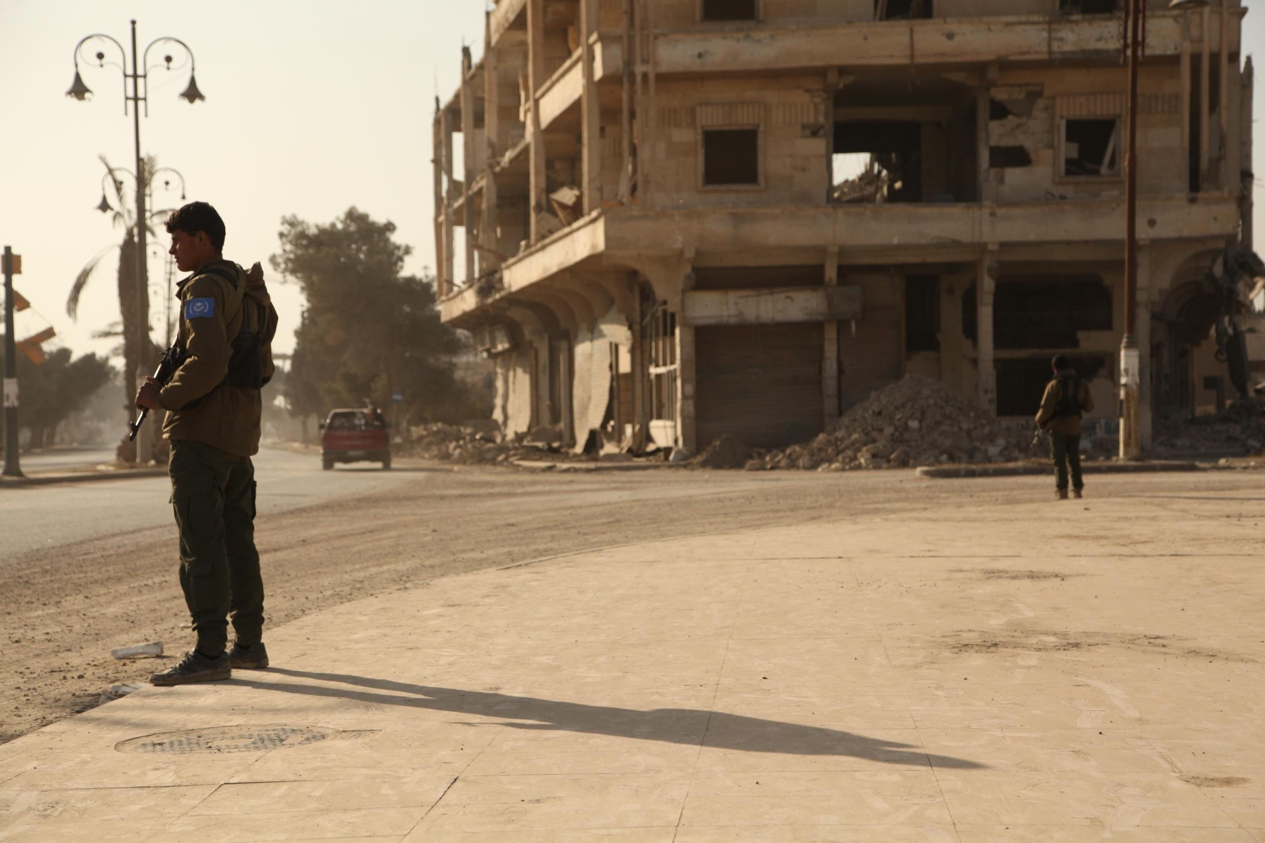 Members of the newly formed RISF or Raqqa Internal Security Force stand guard on a street.