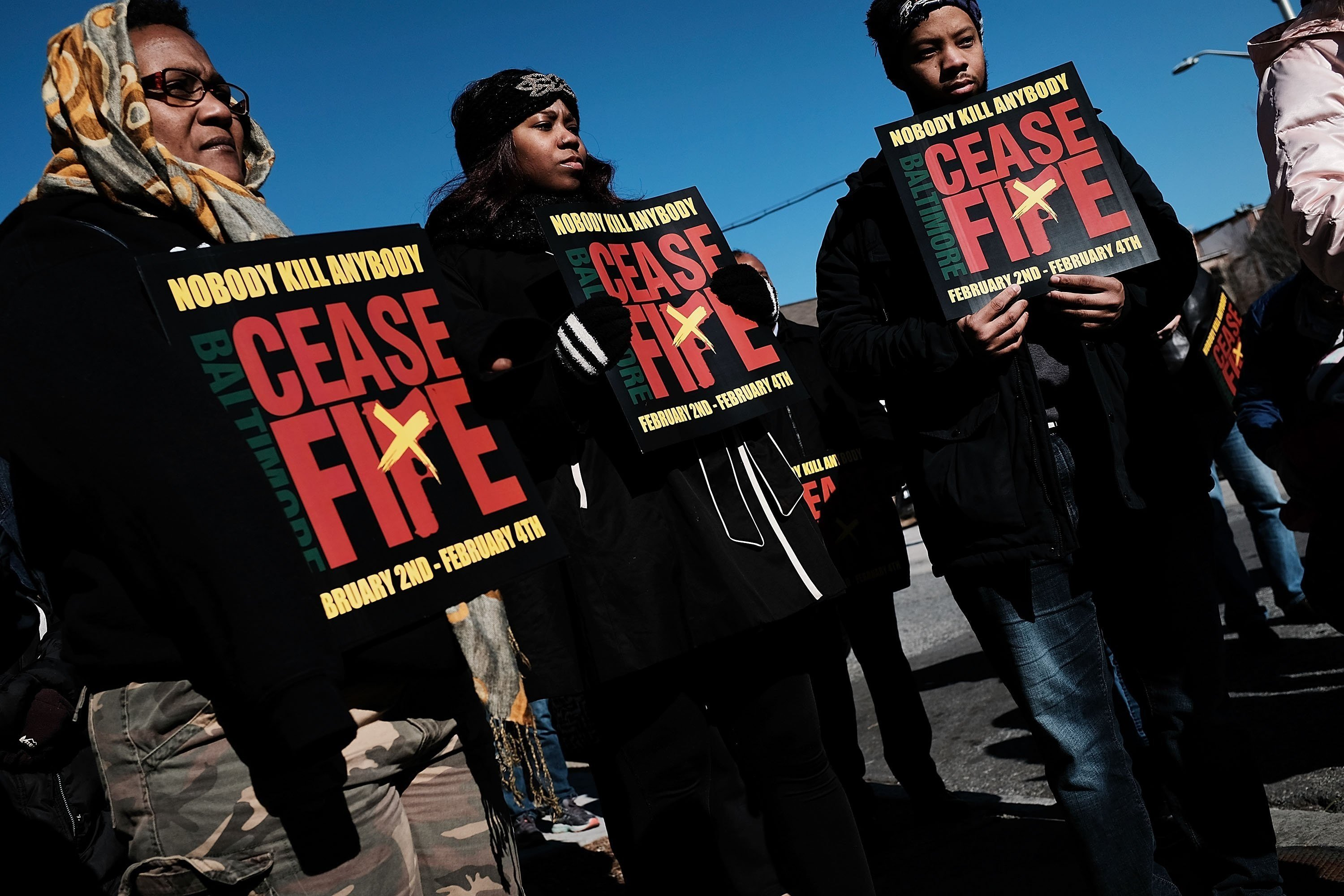 "Activists and residents participate in a ""Peace and Healing Walk"" in an area with a high rate of homicides in Baltimore on February 3, 2018."