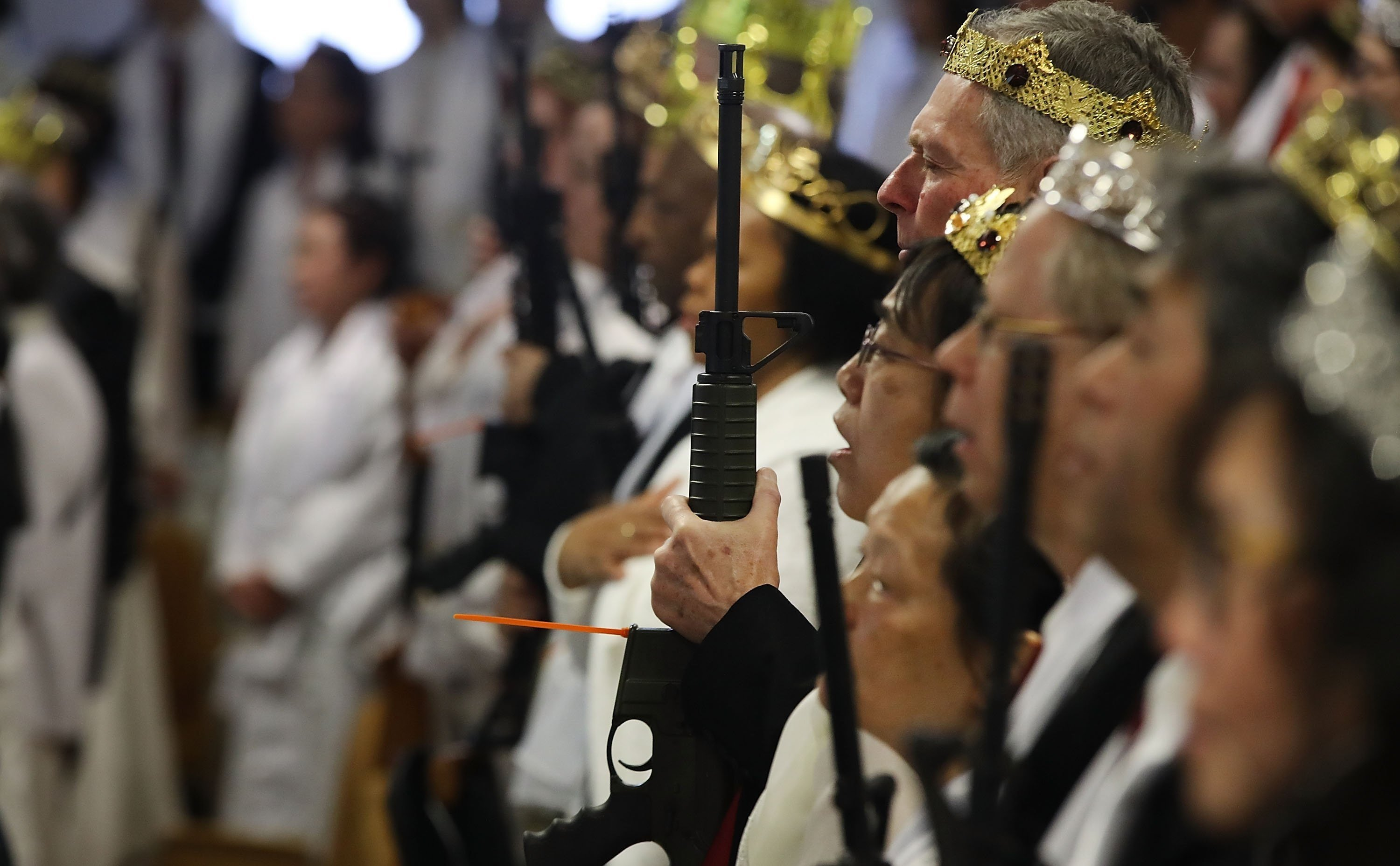 Worshipers clutching AR-15 rifles hold commitment ceremony