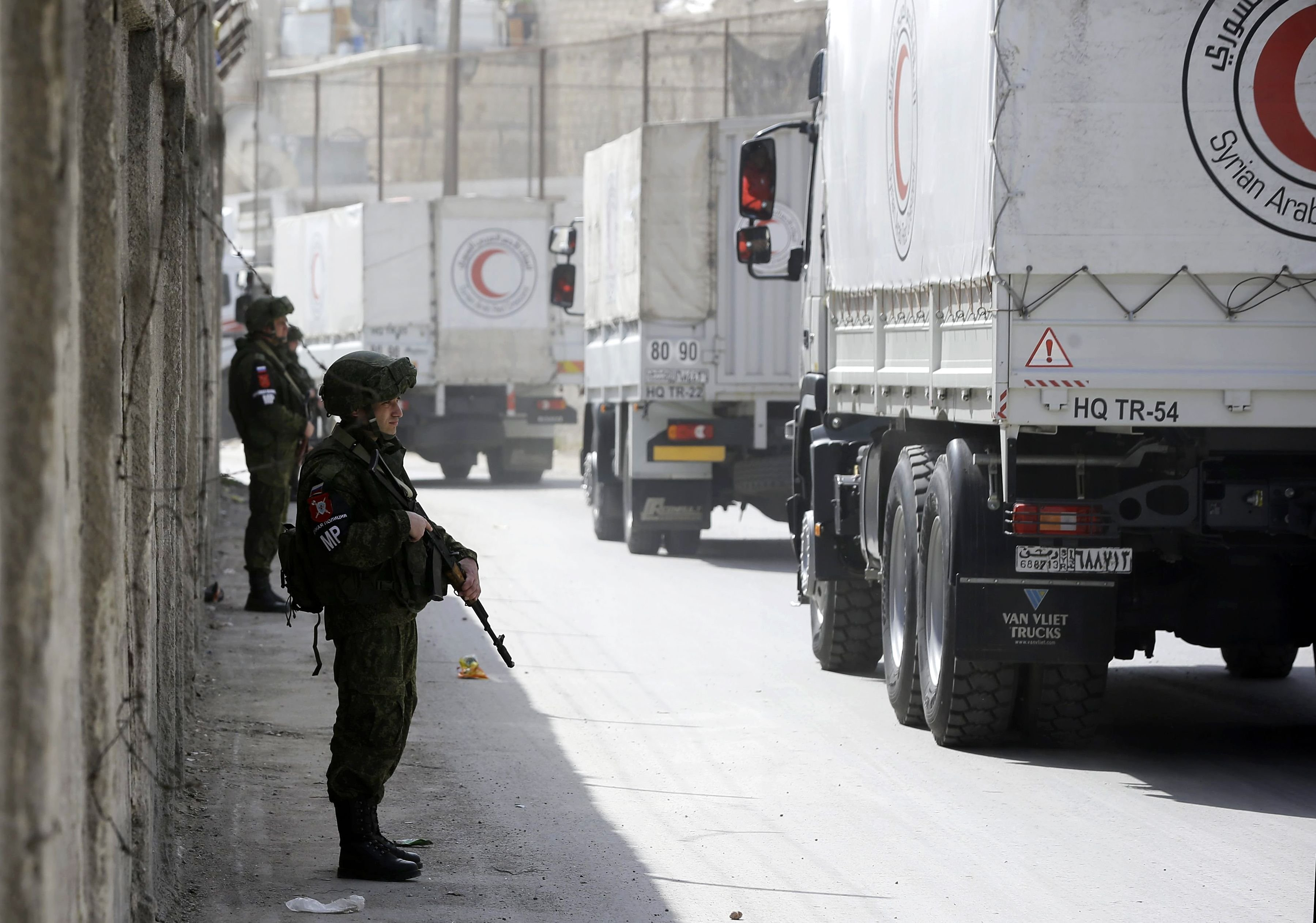 Russian soldiers stand guard as Syrian Arab Reb Crescent trucks carry aid to Eastern Ghouta.  CREDIT: LOUAI BESHARA/AFP/AFP/Getty Images