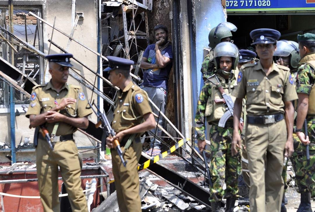 A man looks out from a burned-out home, as Sri Lankan police commandos patrol on the streets of Pallekele, a suburb of Kandy, on March 6, 2018.