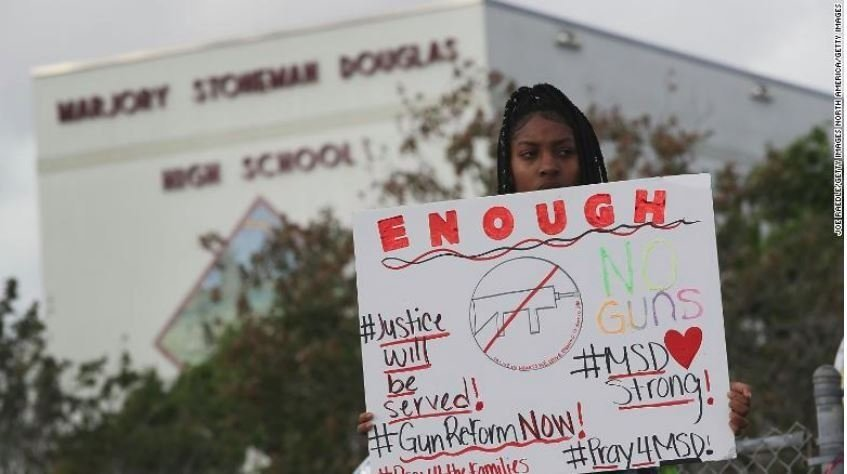A student stands outsid f Marjory Stoneman Douglas High School in Parkland, Florida, protesting gun reform.
