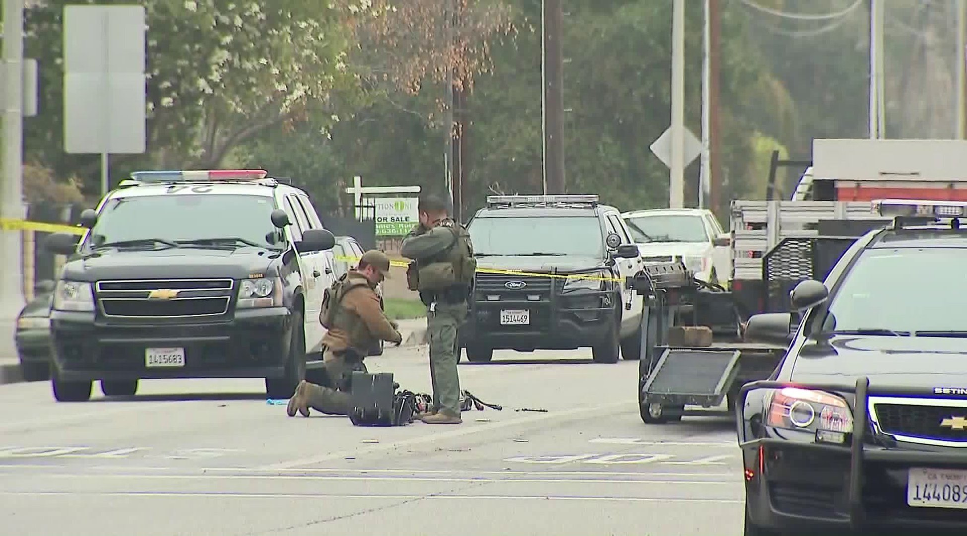 Law enforcement officers are shown near the scene of a barricaded suspect incident in Pomona