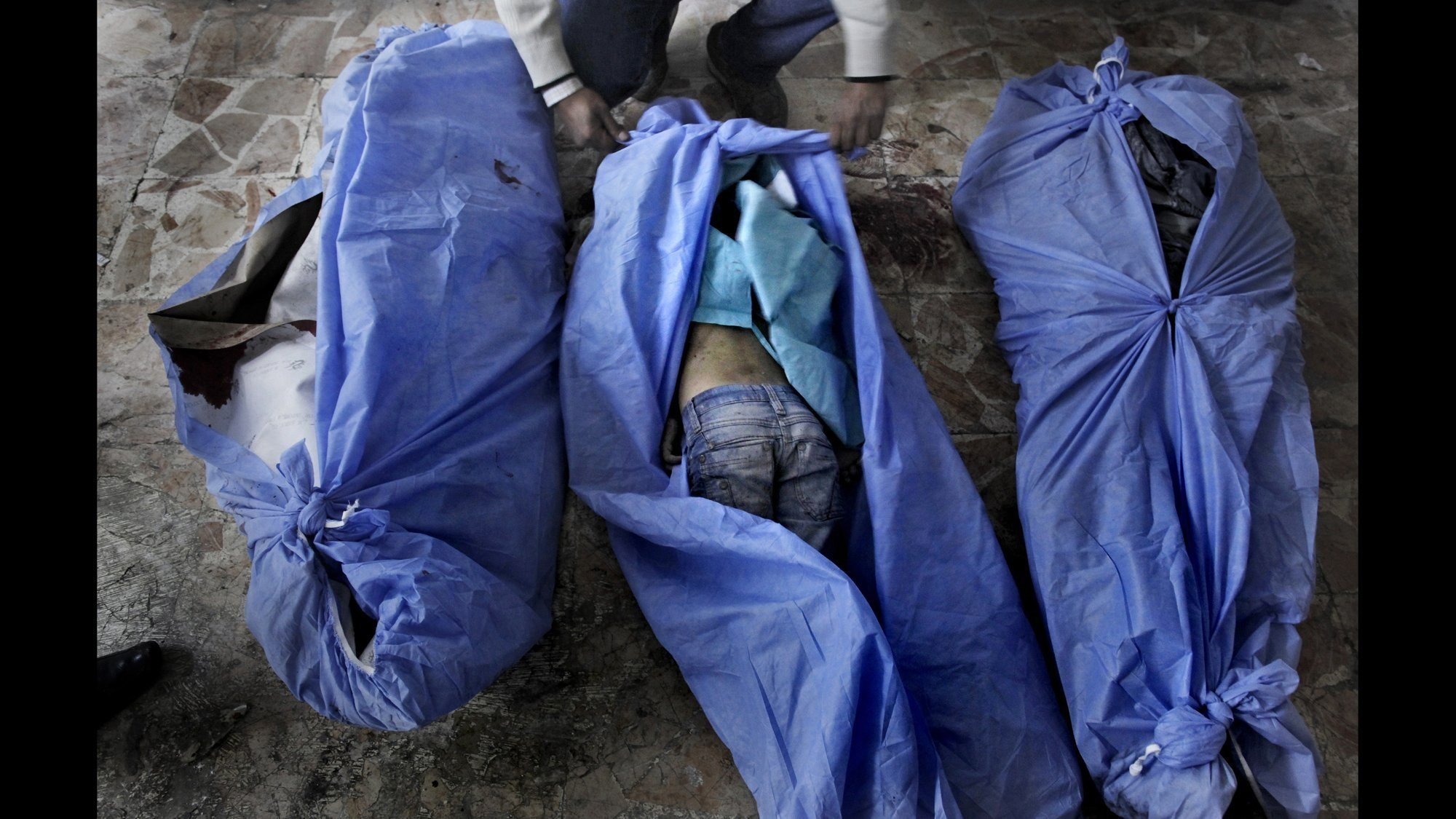 The bodies of three children are laid out for identification by family members at a makeshift hospital in Aleppo in 2012.