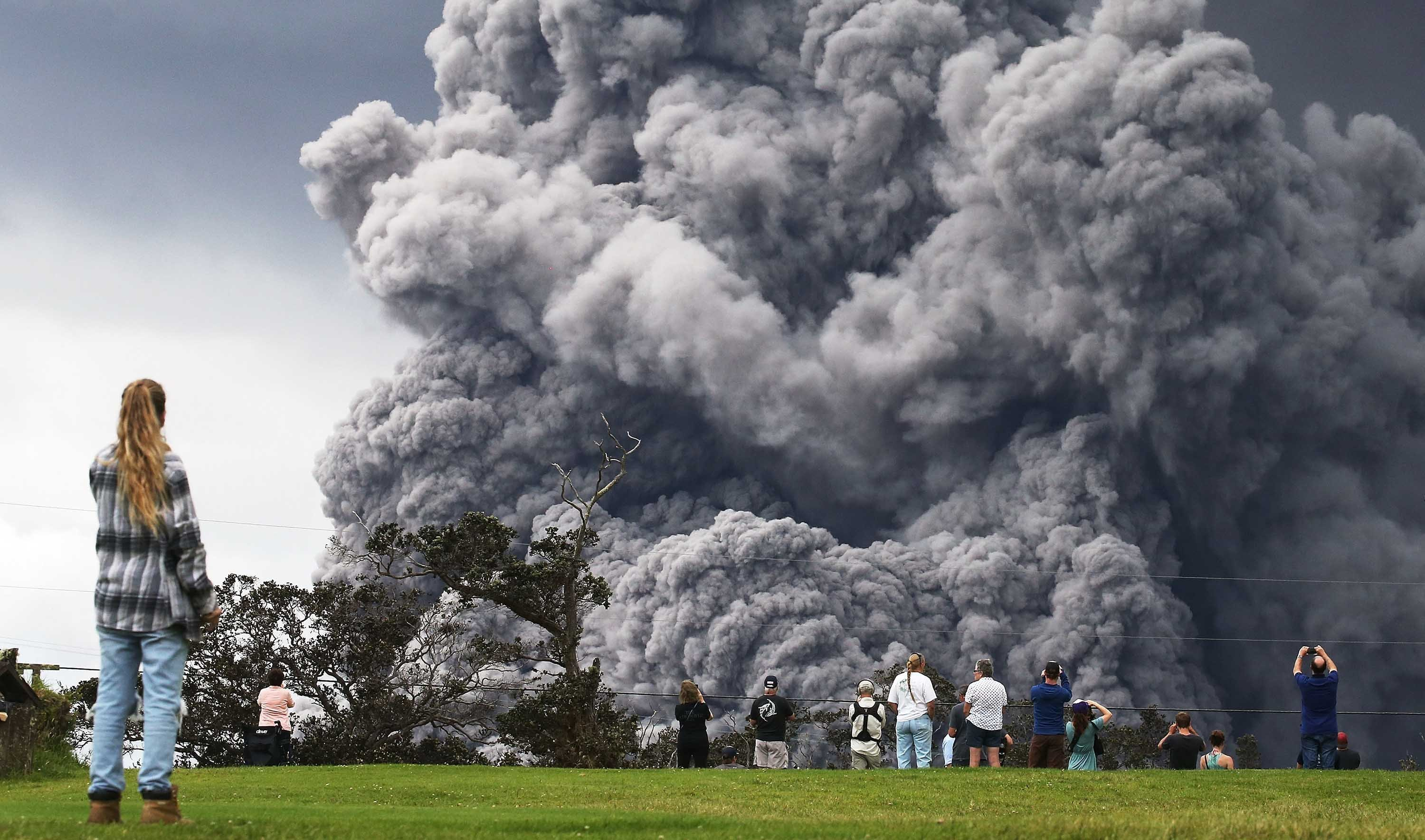 People watch at a golf course as an ash plume rises in the distance from the Kilauea volcano on Hawaii's Big Island on Tuesday.