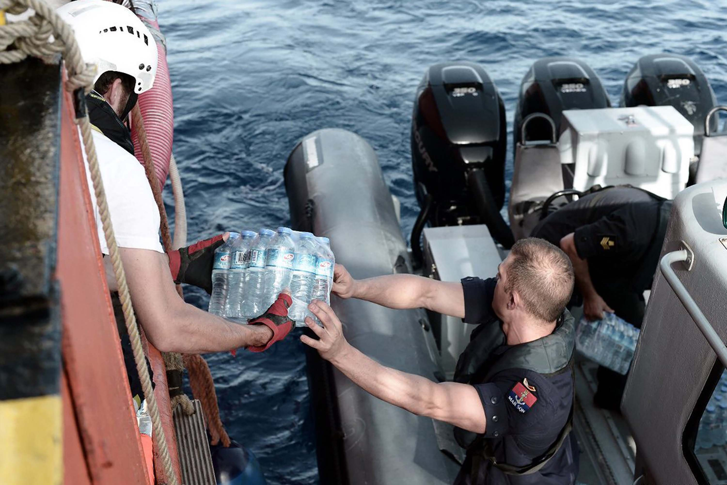 A Maltese maritime officer distributes packs of water to the stranded ship.