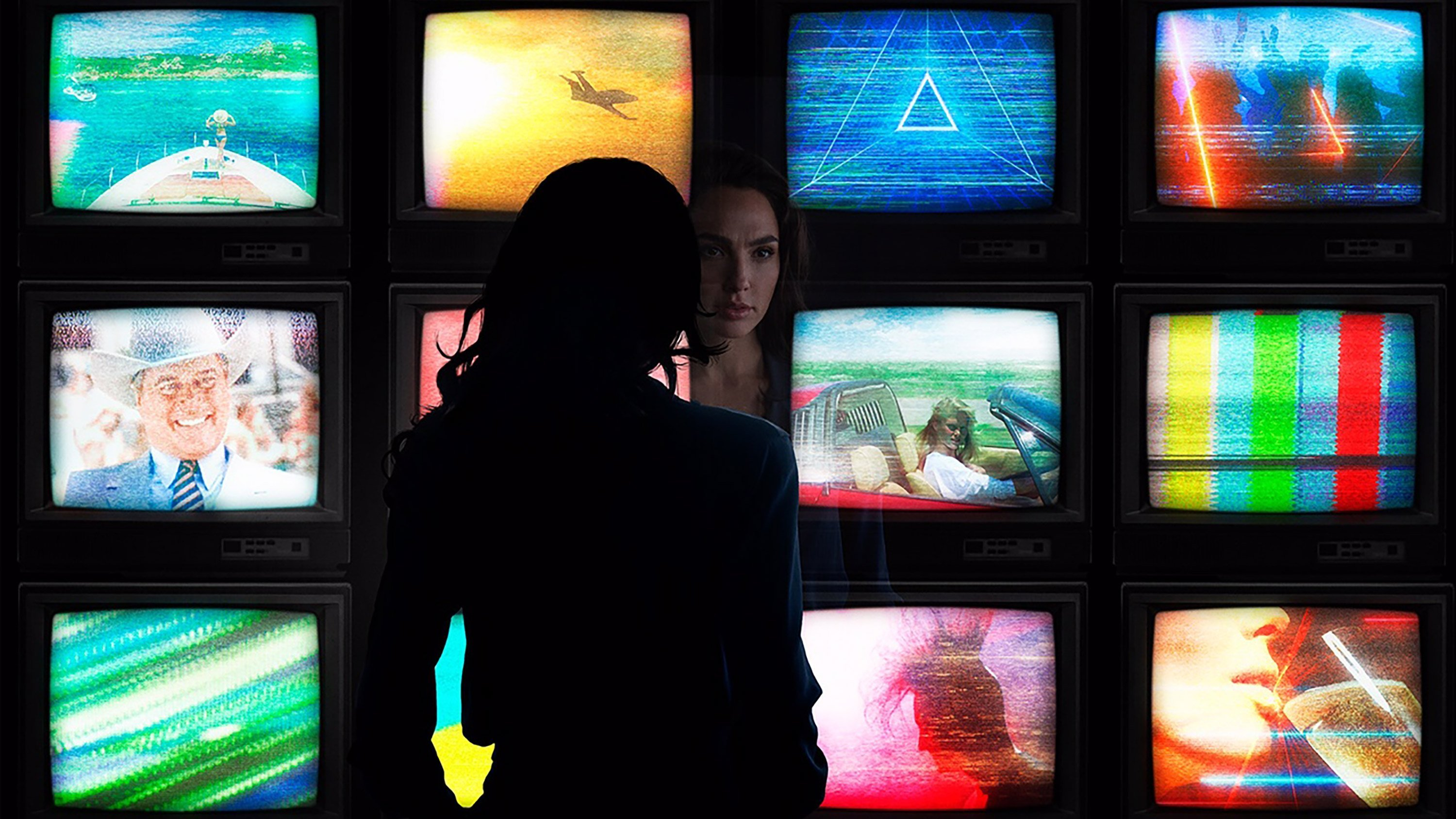 """A photo of """"Wonder Woman 1984"""" features star Gal Gadot standing in front of a several television sets -- all of which are playing iconic pop culture moments from the decade."""