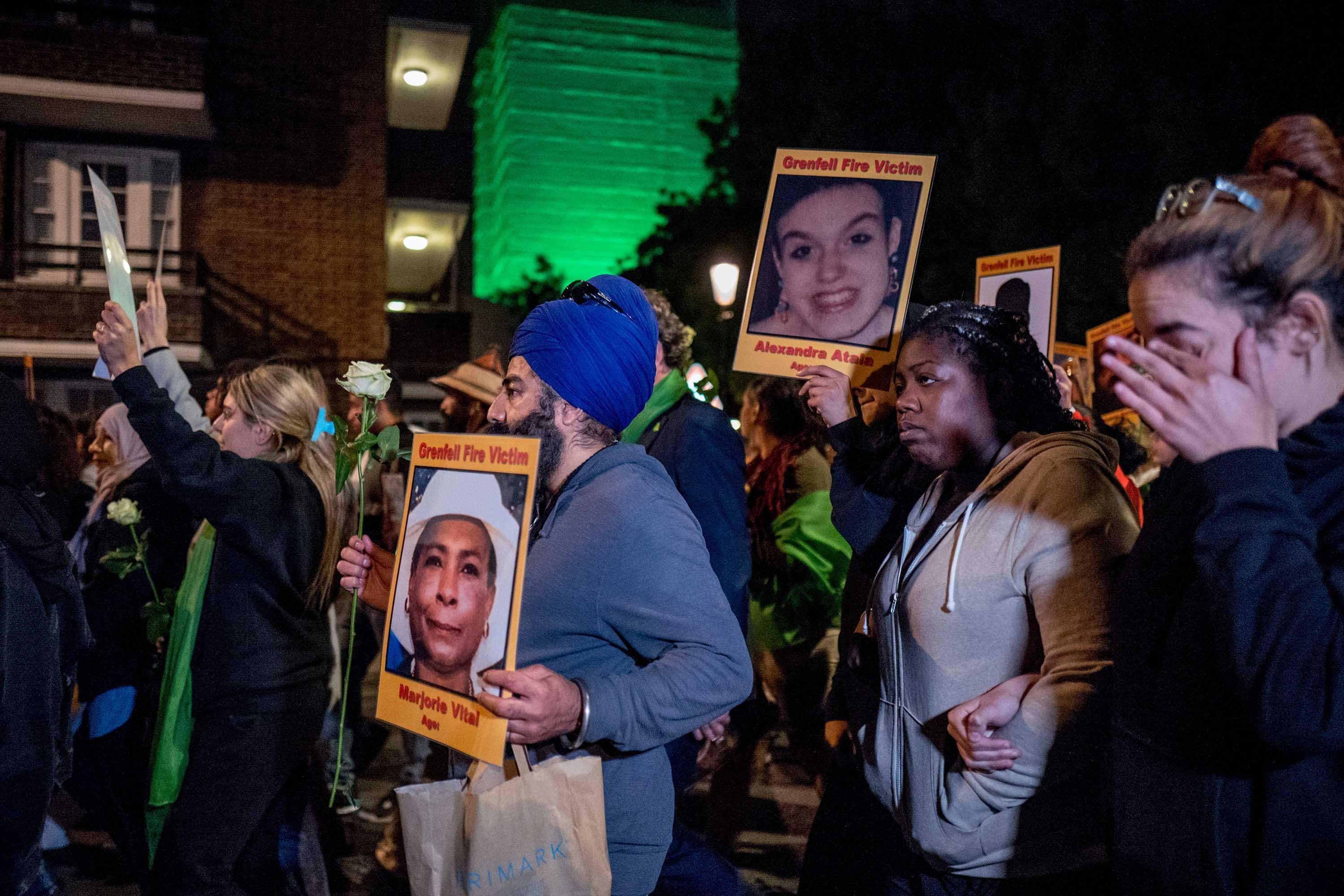 Families and friends who lost loved ones in the fire hold portraits of victims as they march to the illuminated Grenfell Tower in the early hours of Thursday.