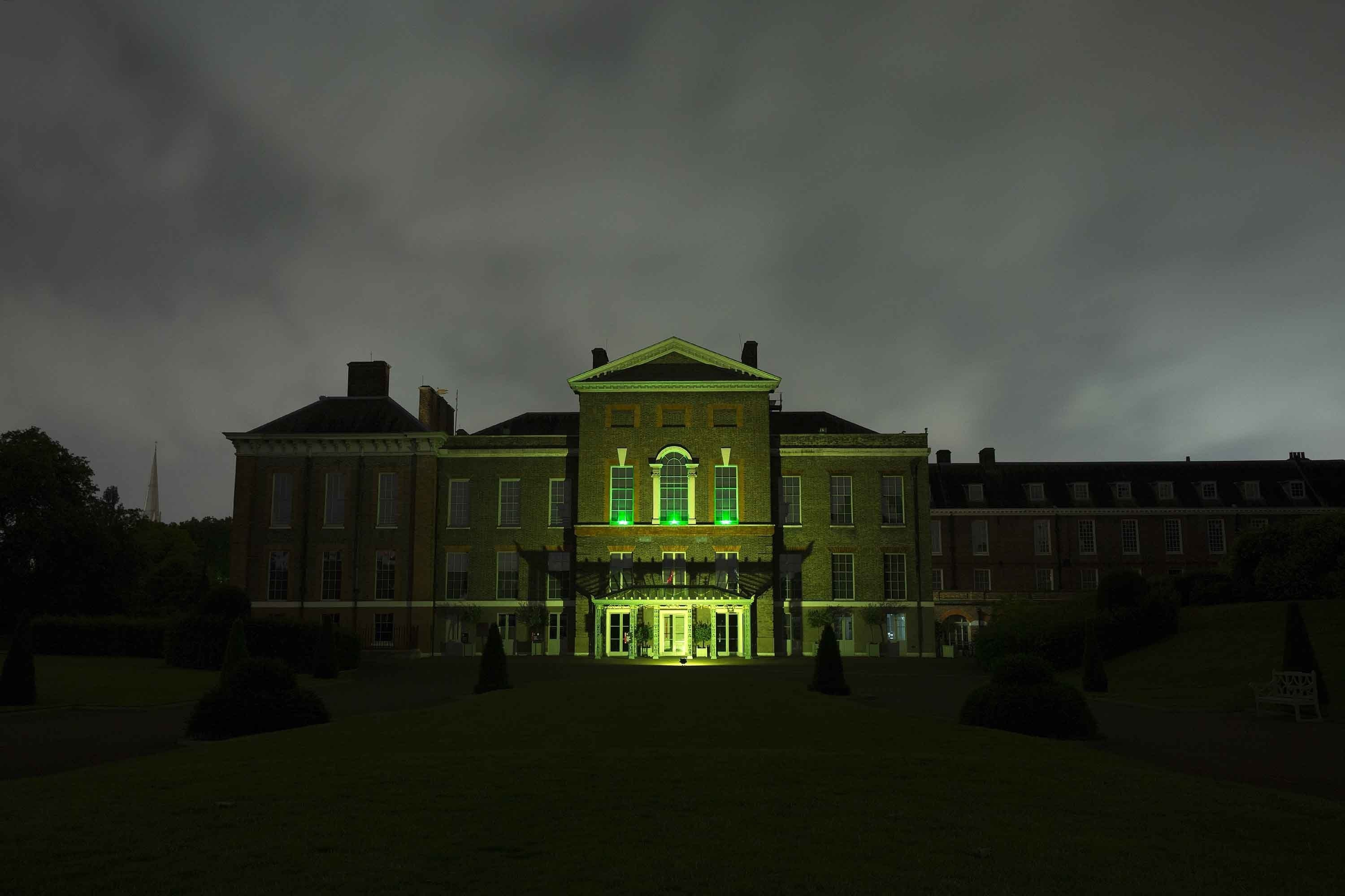 Kensington Palace's East facade is lit up in green to show support for survivors of the fire.
