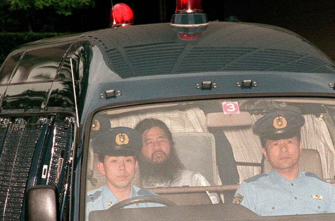 In this picture taken on July 19, 1995, Shoko Asahara (C), head of the doomsday cult Aum Shinrikyo, is transferred from Tokyo police headquarters to Tokyo District Court for questioning.