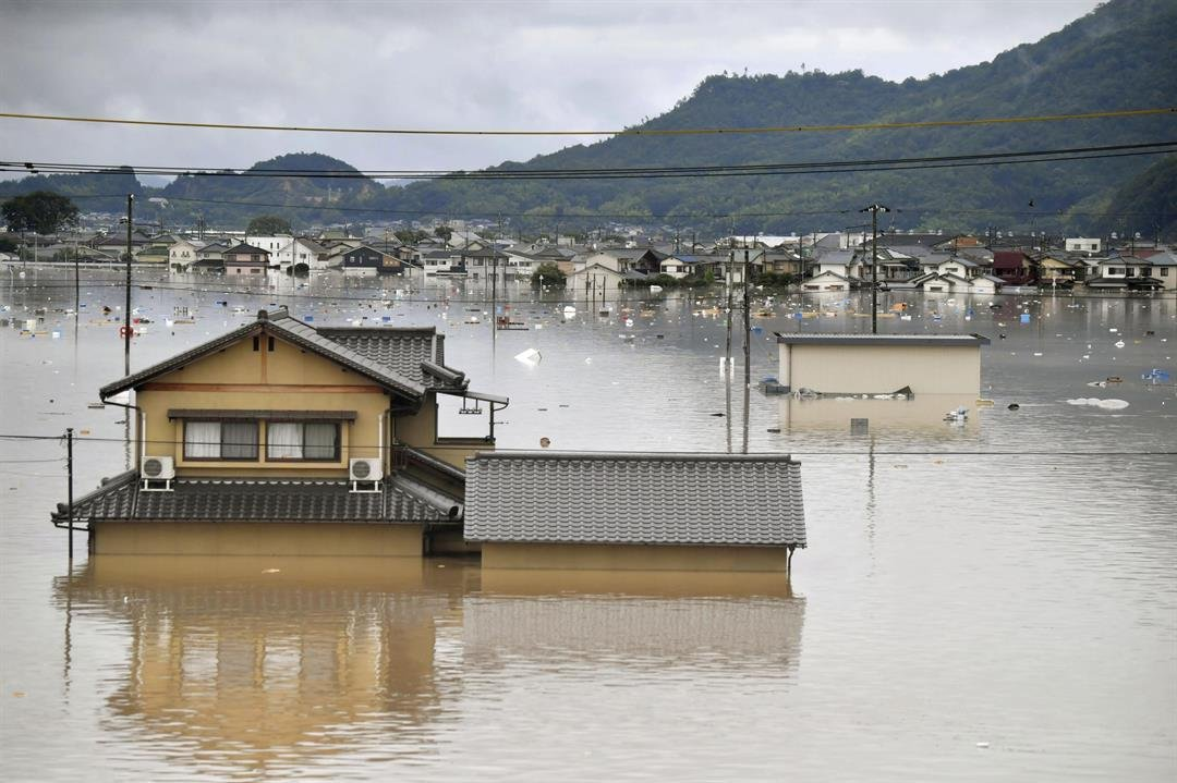 Residential buildings are partially submerged in floodwaters caused by heavy rains in Kurashiki, Okayama prefecture, southwestern Japan, Saturday, July 7, 2018.