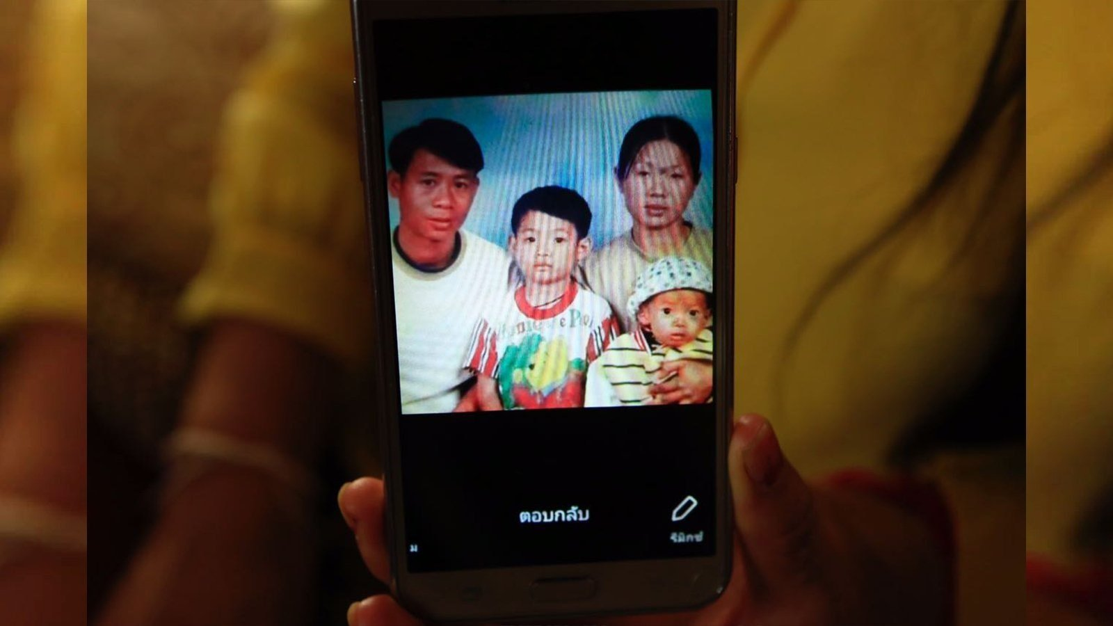 Soccer coach Ekkapol Ake Chantawong, seen here as a boy in the center of this photo with his late parents and younger brother.