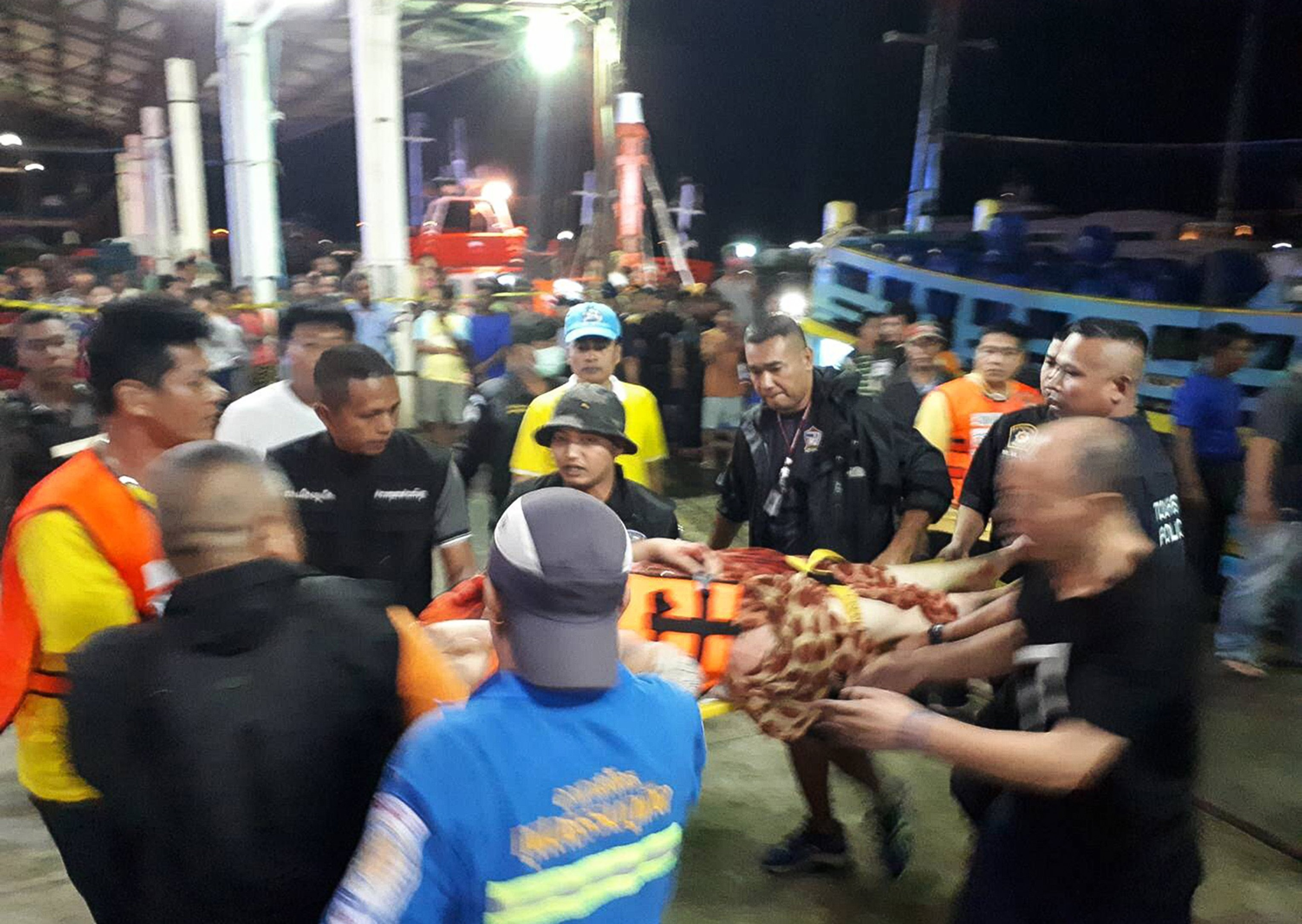 Thai rescue and paramedic personnel attend to rescued passengers of capsized tourist boat in rough seas at a port in Phuket on Thursday.