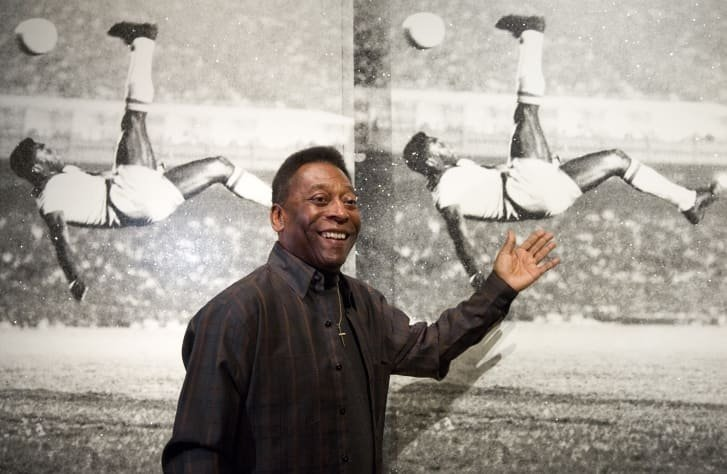 "Brazilian football legend Pelé poses in front of ""Pelé, Bicycle Kick"" by artist Russell Young at London's Halcyon Gallery in 2015."