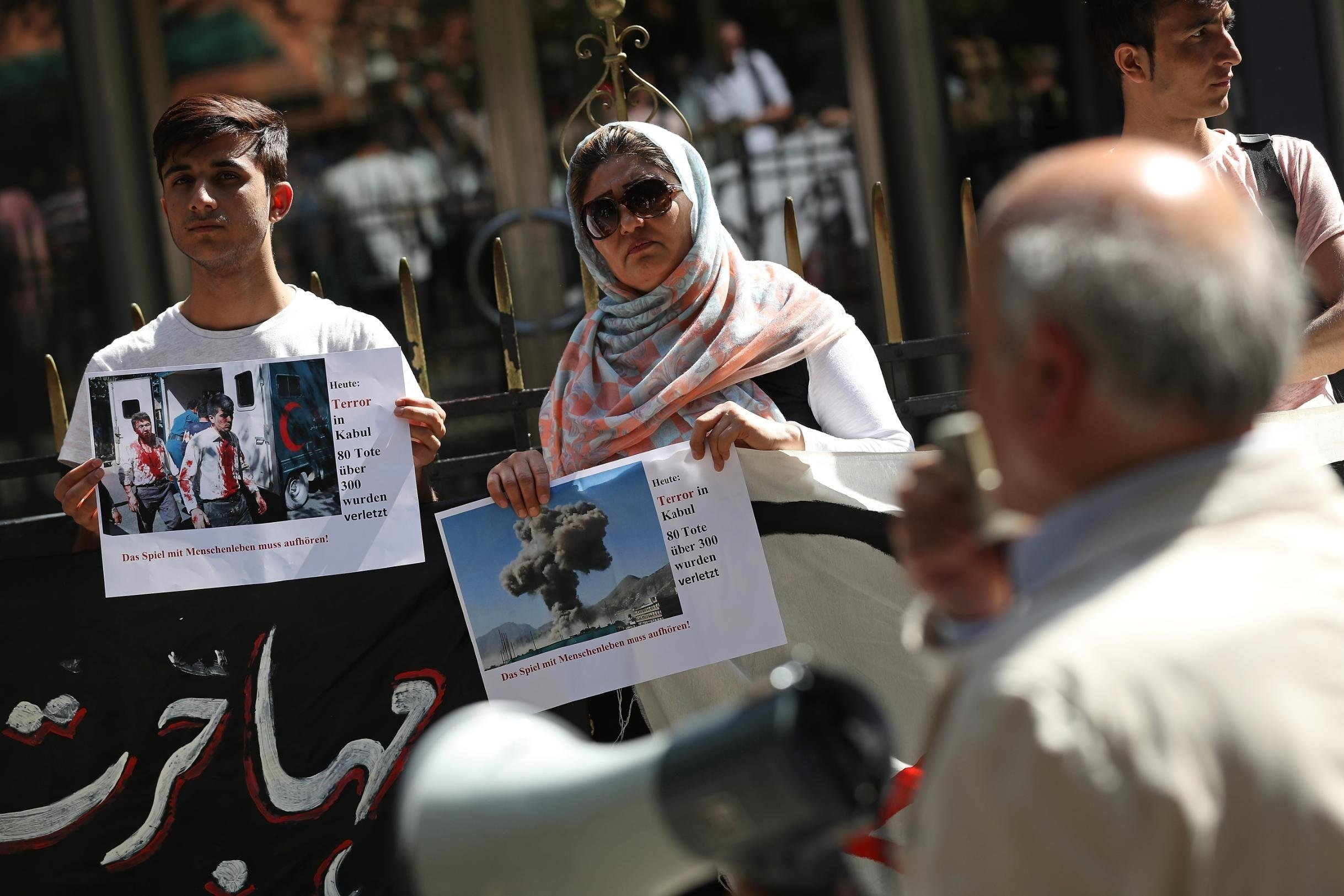 Afghans protesting against deportations in Berlin in May 2017 hold up photos of a bombing in Kabul.