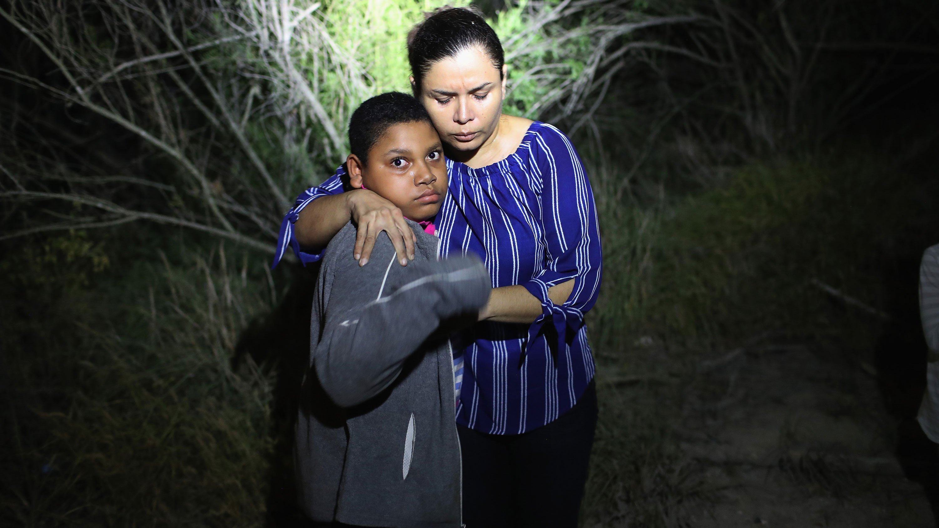 A mother and son from Honduras are found in the dark near the US-Mexico border in McAllen, Texas. The asylum seekers had rafted across the Rio Grande from Mexico and got lost in the woods.