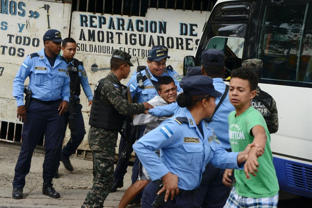 "Honduran police hold a boy whose father was killed in 2016 by alleged gang members for refusing to pay them a ""war tax."""
