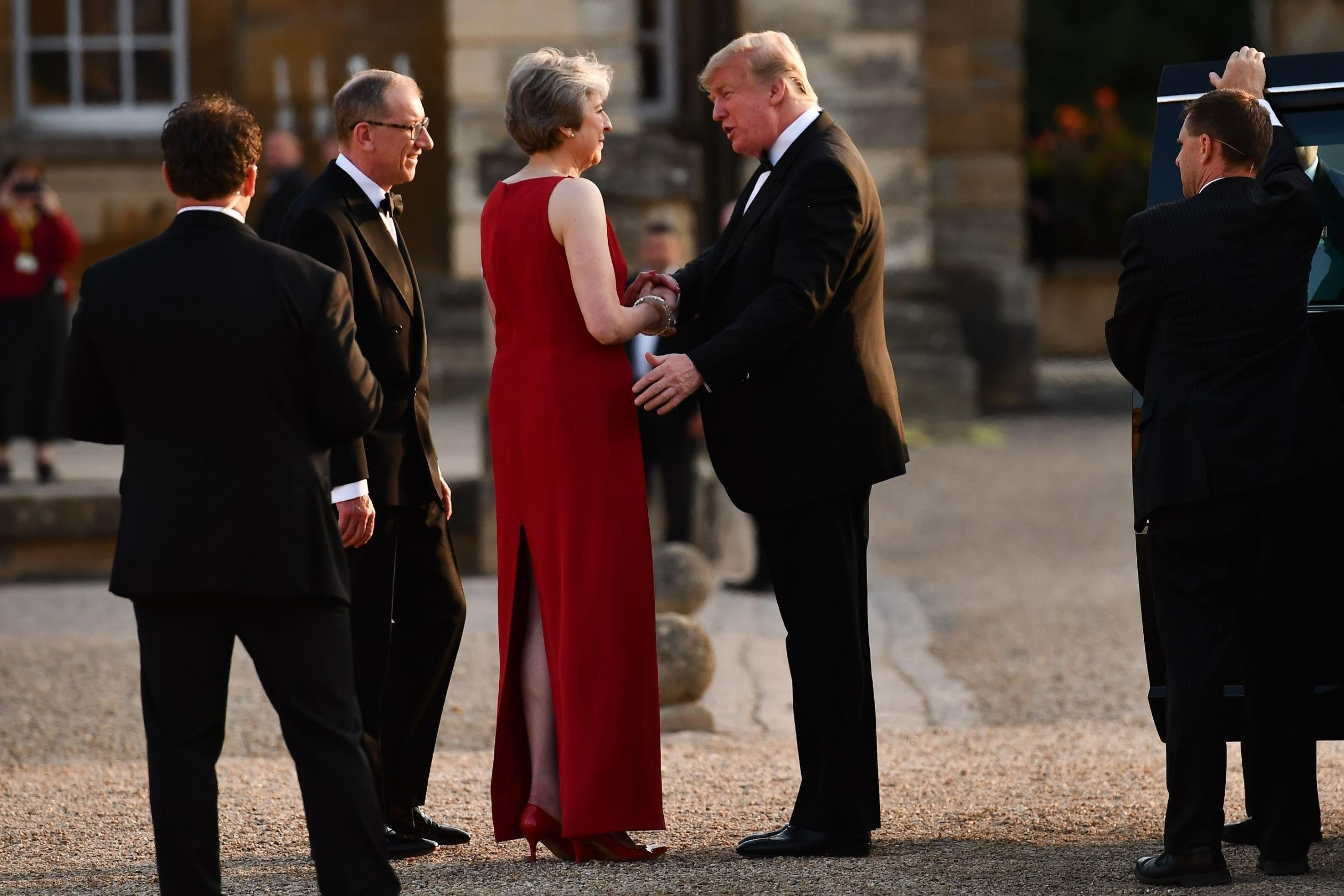 Britain's Prime Minister Theresa May (C) shakes hands with US President Donald Trump (R) as Philip May (L) looks on as she welcomes Trump and his wife US First Lady Melania Trump (unseen) for a black-tie dinner with business leaders at Blenheim Palace,...