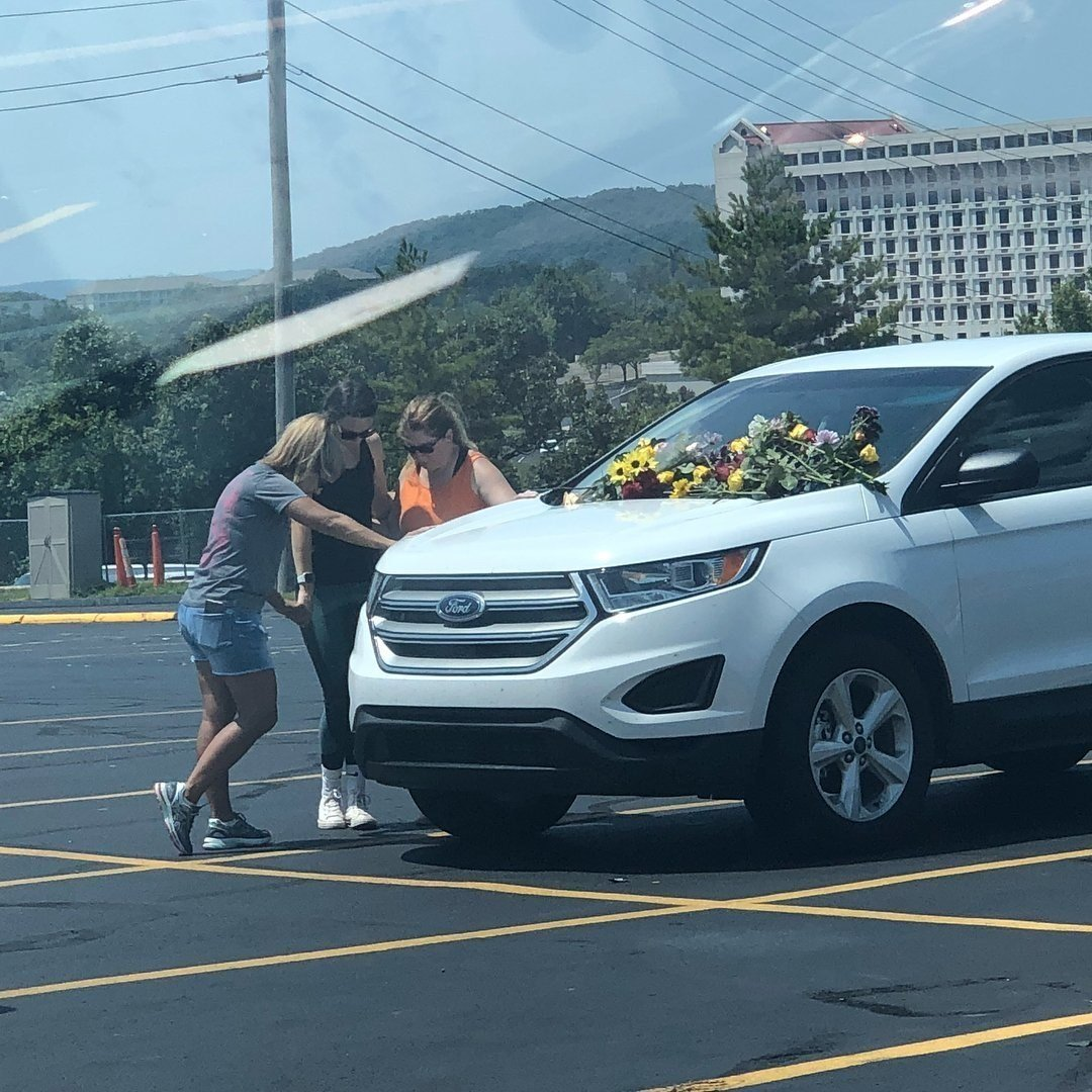 Mourners place flowers on the windshield of cars left in the parking lot of Ride the Ducks