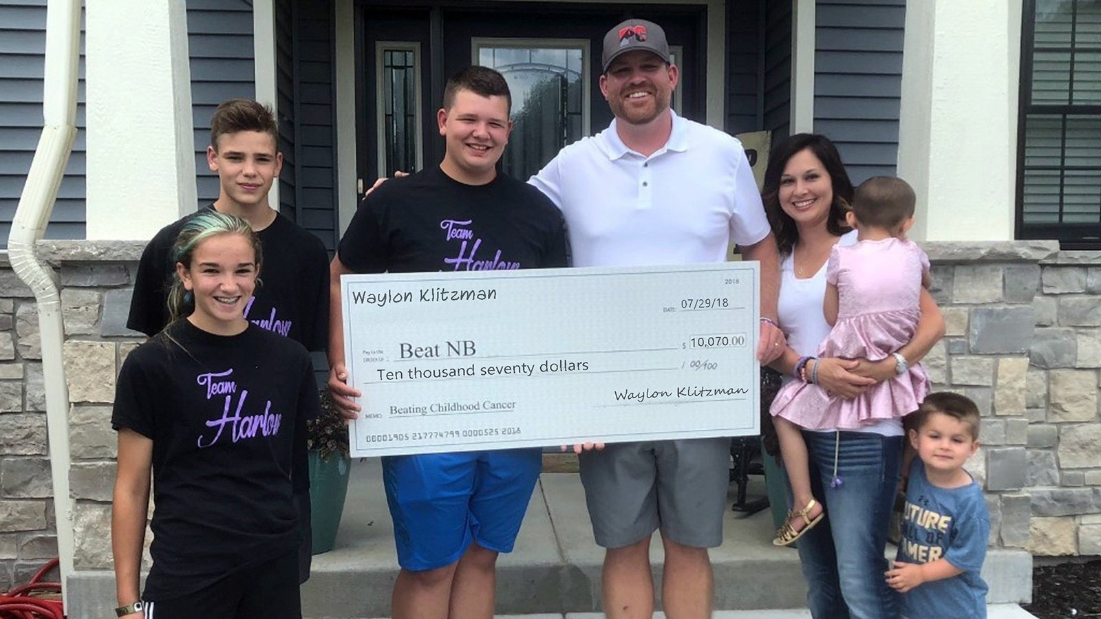 Waylon Klitzman delivers a $10,000 check to cancer patient Harlow Phillips' family.