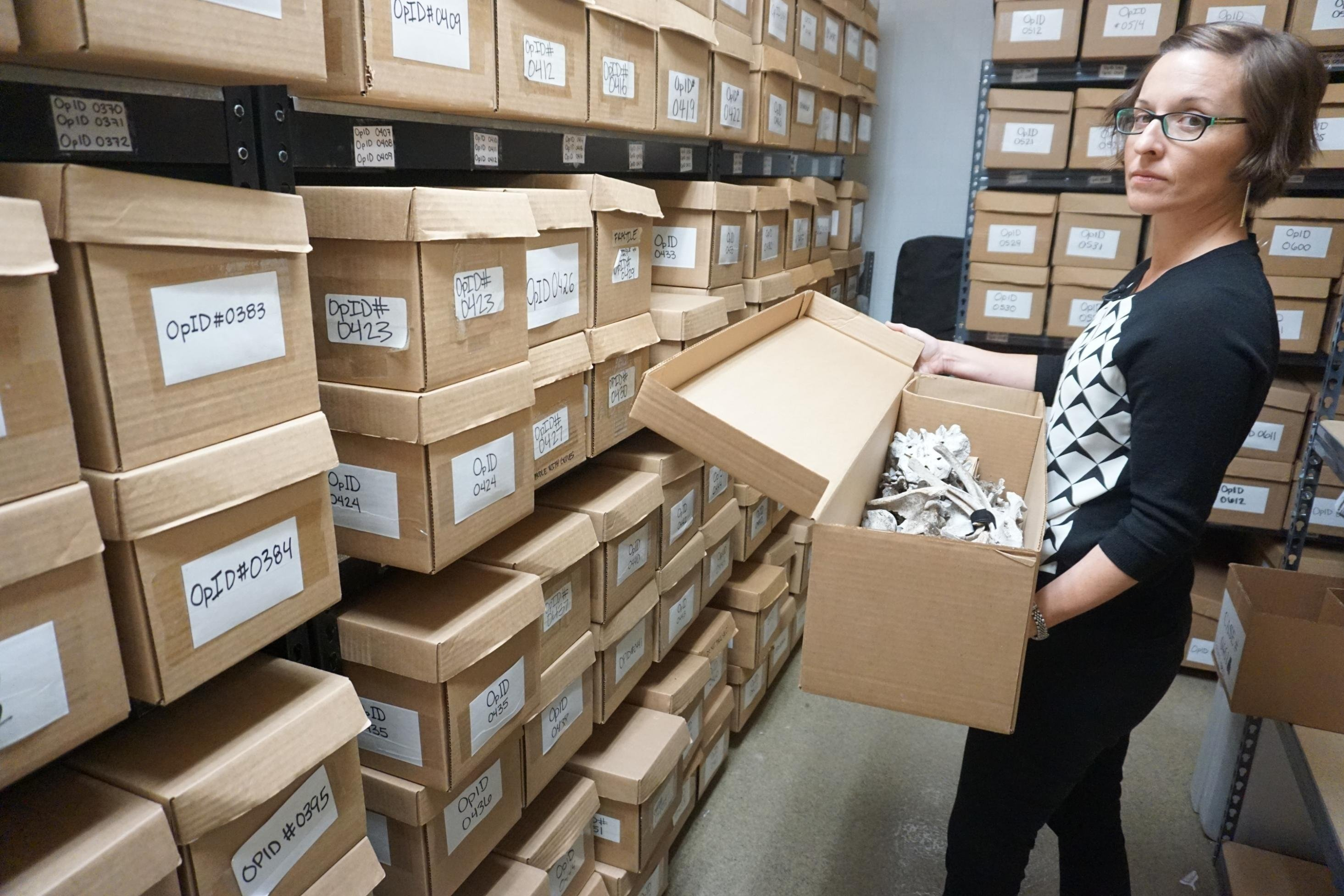 Kate Spradley, a forensic anthropologist in her lab at Texas State University, is trying to identify hundreds of bodies. Each box holds the remains of one person who died migrating to the United States.