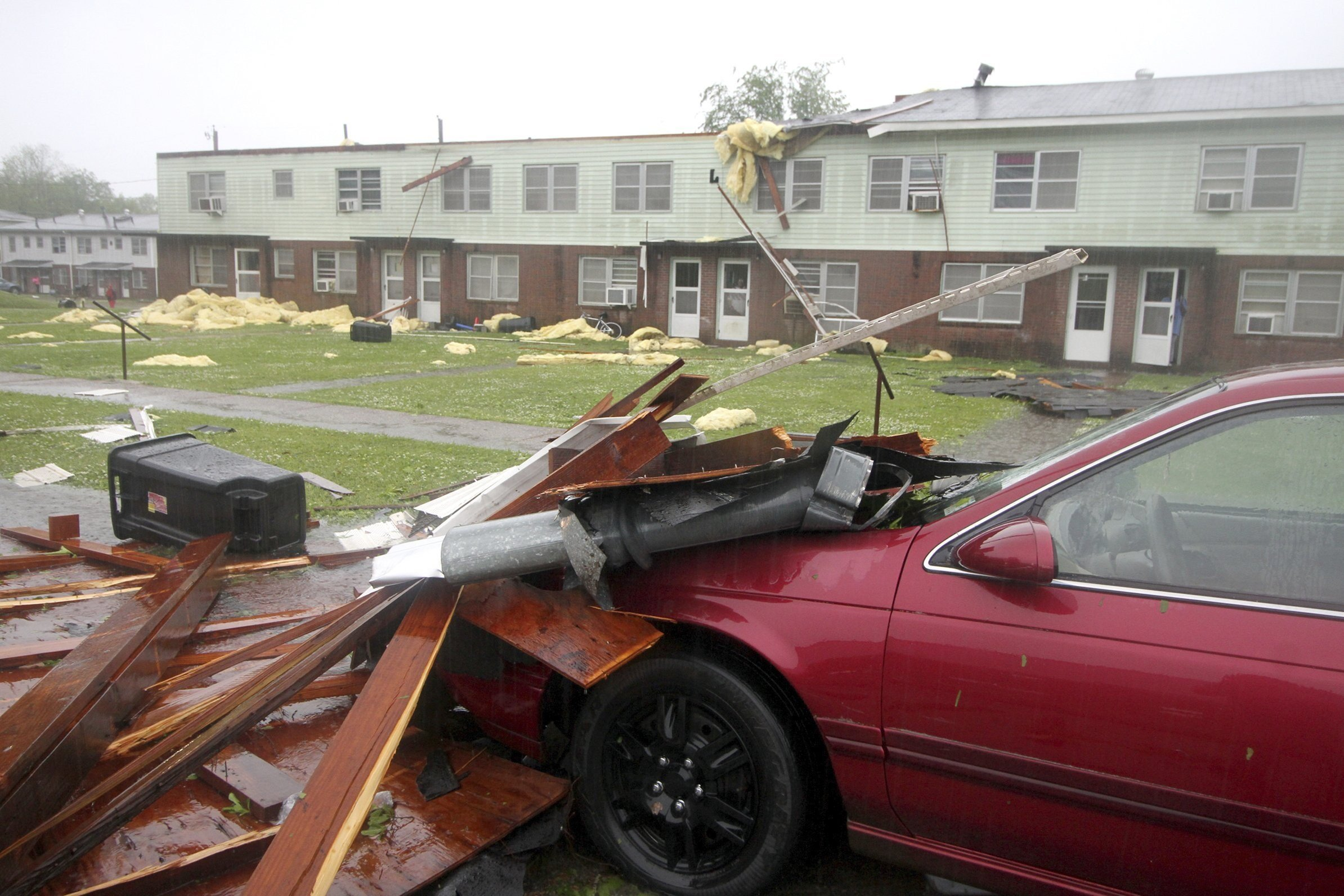 A parked car covered in debris sits next to an apartment complex in Meridian, Mississippi, after a possible tornado hit the area Saturday, April 14, 2018.