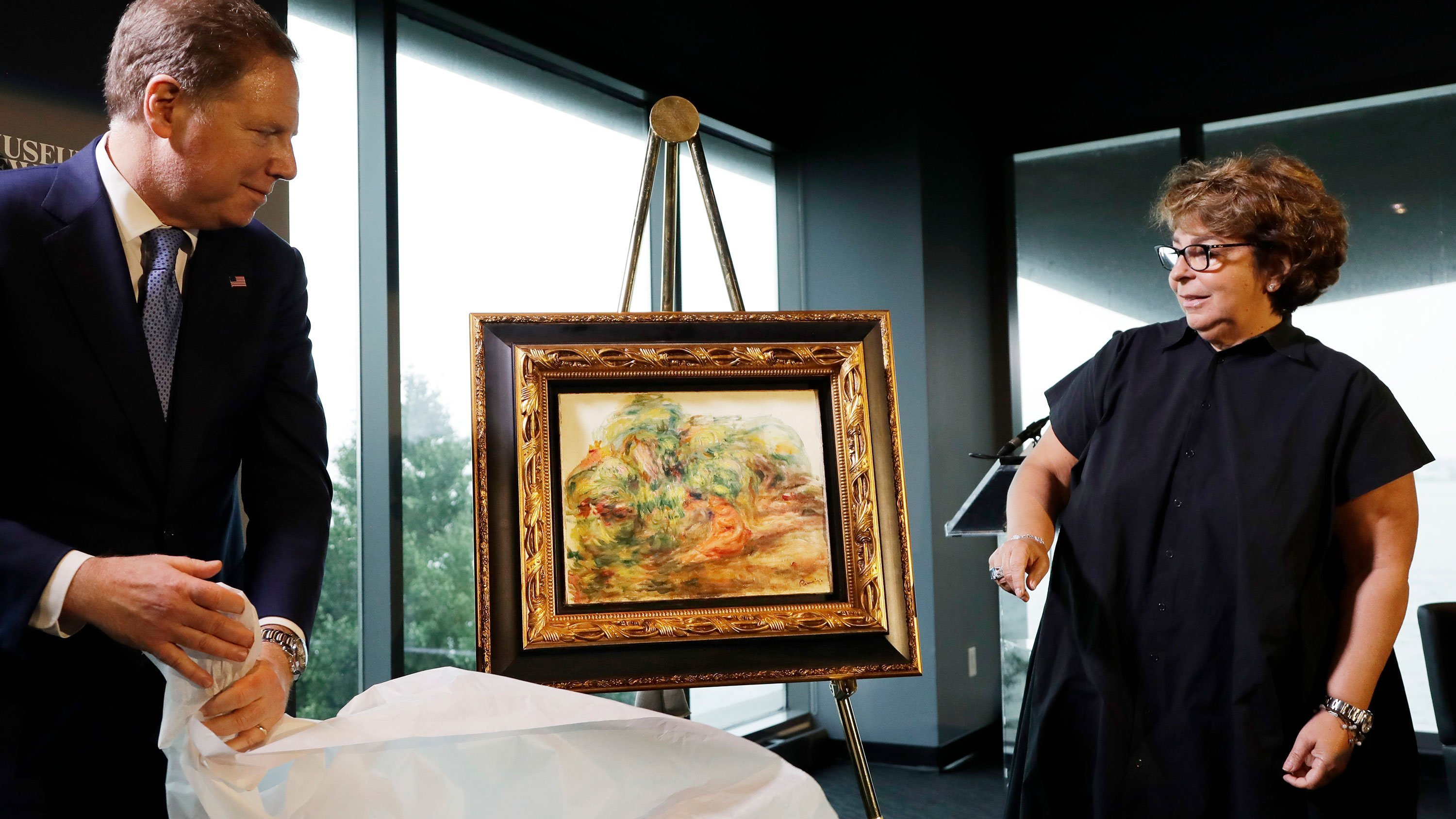 US Attorney Geoffrey Berman, left, unveils the recovered Renoir painting with Sylvie Sulitzer on Wednesday.