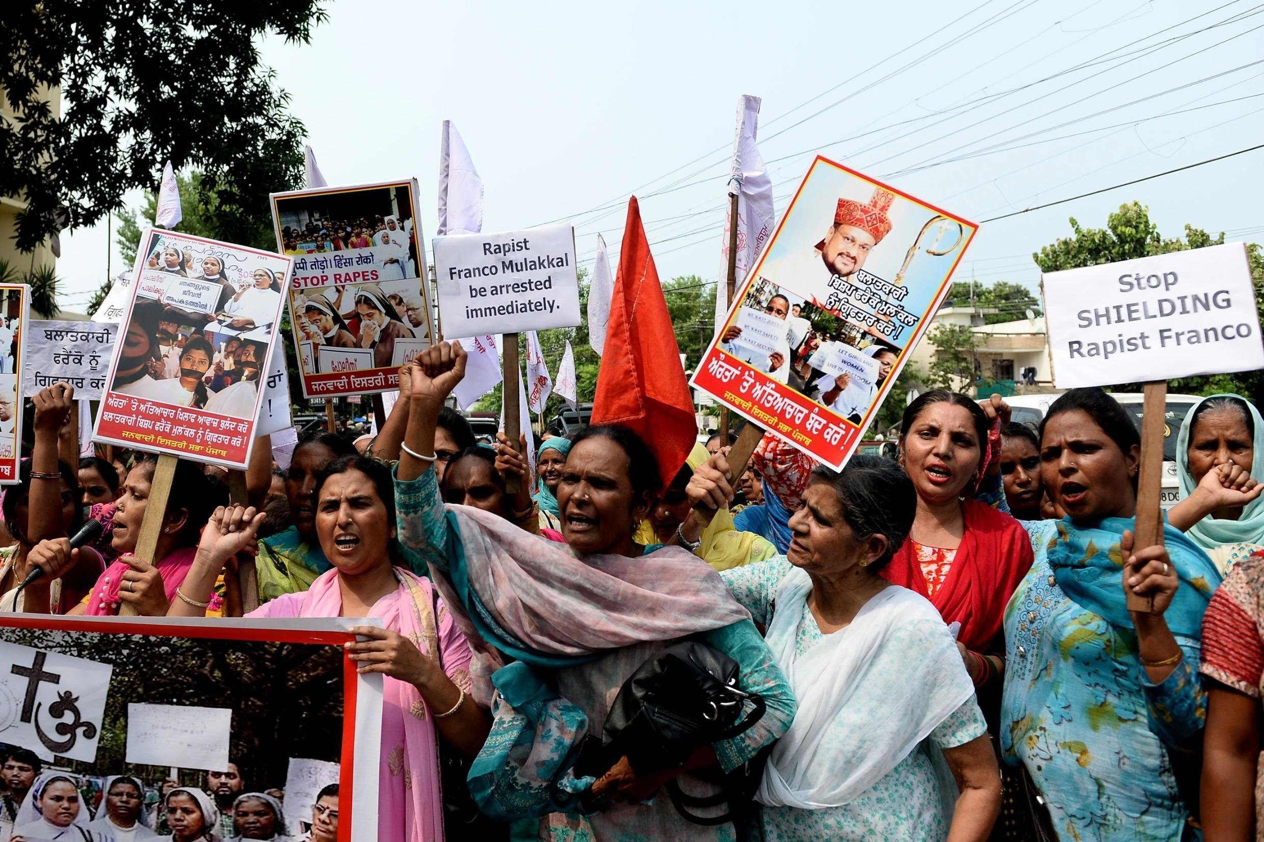 Indian women in Jalandharhold placards and chant slogans during protest march to demand the the arrest of Roman Catholic church Bishop Franco Mullakal, who is accused of raping a nun,.